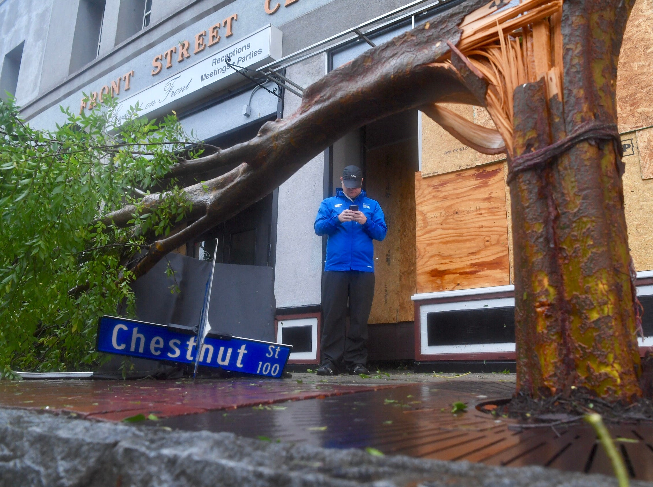 Michael Vann of The Weather Channel  stands near a fallen tree in downtown Wilmington, N.C., on Friday, Sept. 14, 2018, in the aftermath of Hurricane Florence's landfall.