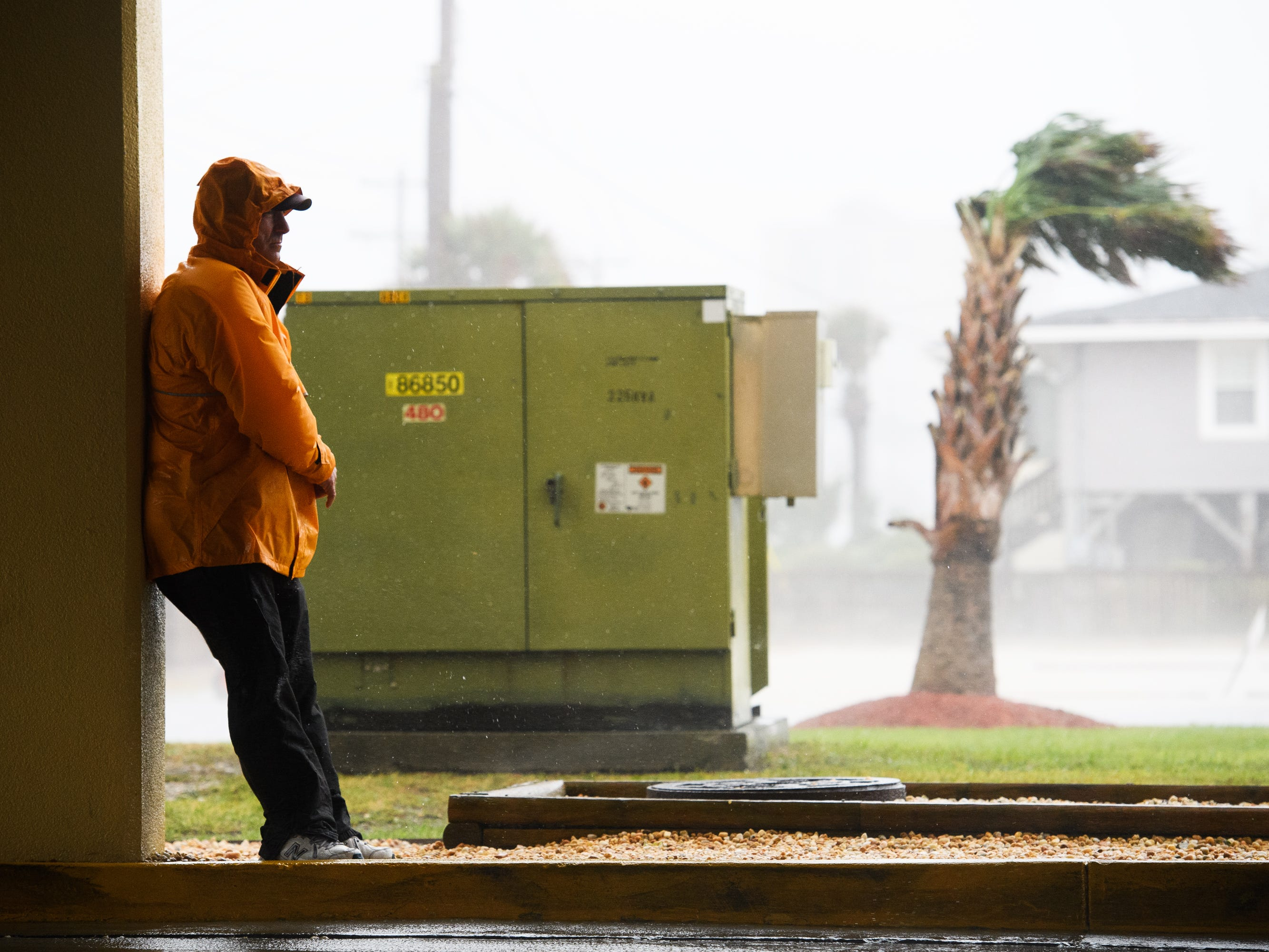 Steve Mann, operational manager for the Cherry Grove Pier, waits for wind gusts to decrease before advancing into a parking structure in North Myrtle Beach on Friday, Sept. 14, 2018.