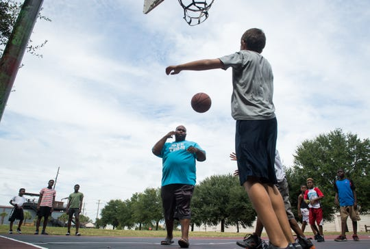 9/13/18 1:58:47 PM -- Charleston, SC, U.S.A  -- Shamaine Smith, a local youth football coach,  organizes pickup basketball games for local kids whose families are not evacuating Hurricane Florence on the courts along Cool Blow Street in Charleston, SC prior to the Hurricane Florence making landfall.  --    Photo by Jack Gruber, USA TODAY staff