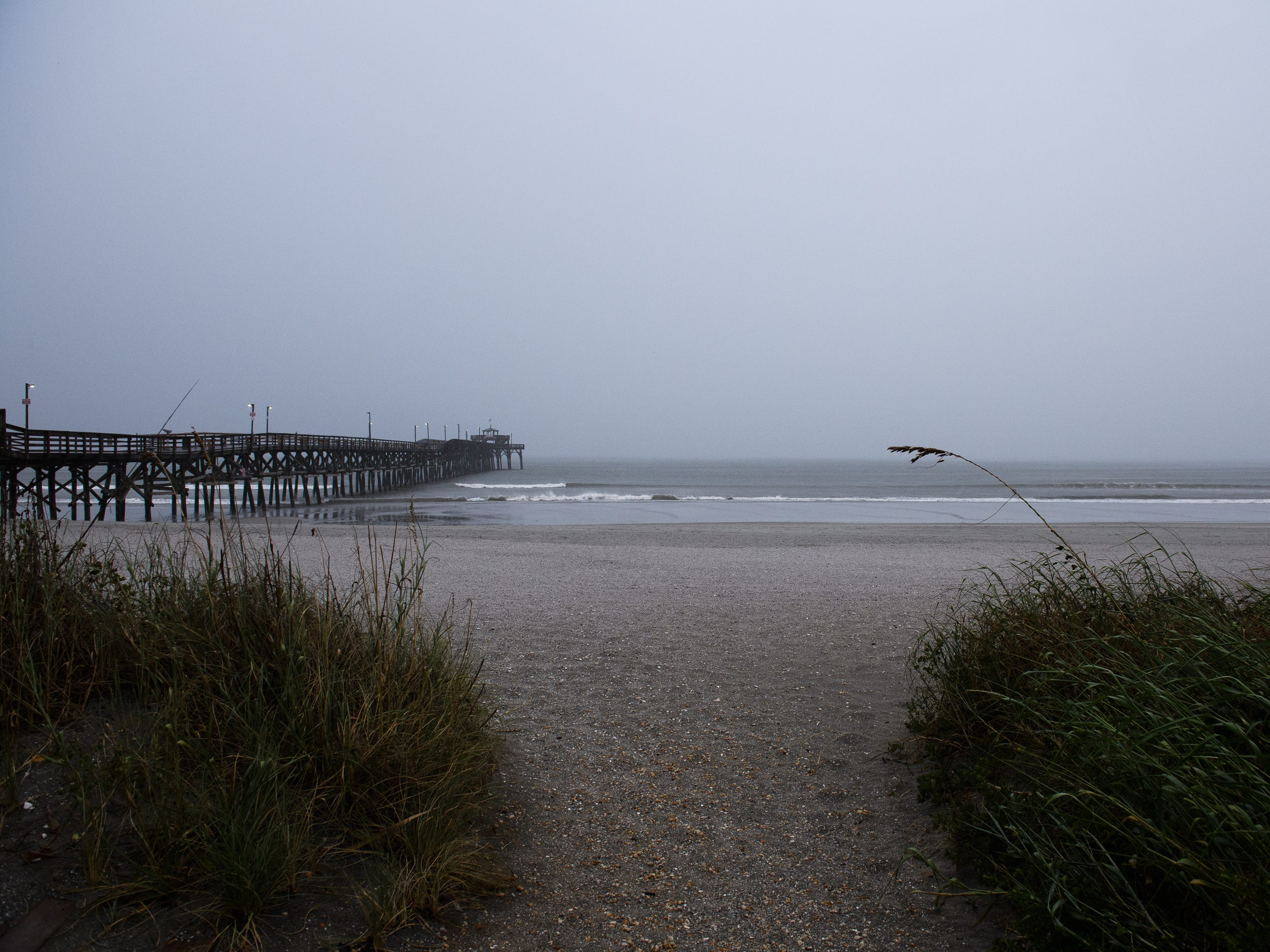 The first rain from a stray outer band of Hurricane Florence hits the Cherry Grove Pier area of North Myrtle Beach on Thursday, Sept. 13, 2018.