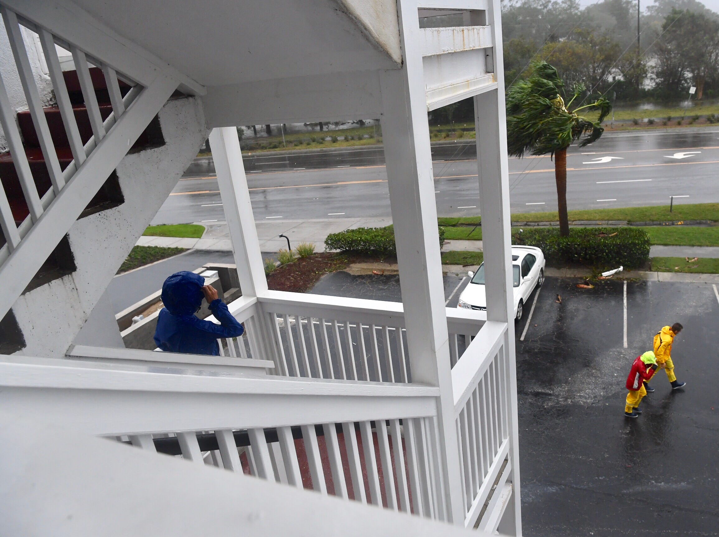 Mary Florian of Wilmington, NC, watches Hurricane Florence pass through while a couple walks by her residence at Waterway Lodge Friday, Sept. 14, 2018.