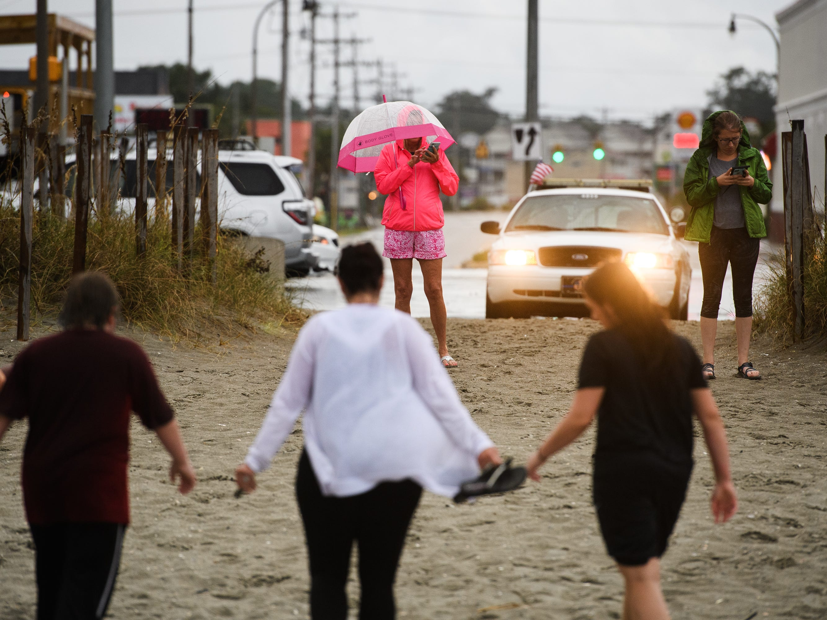Beachgoers leave after being informed of a curfew due to Hurricane Florence on Thursday, Sept. 13, 2018.