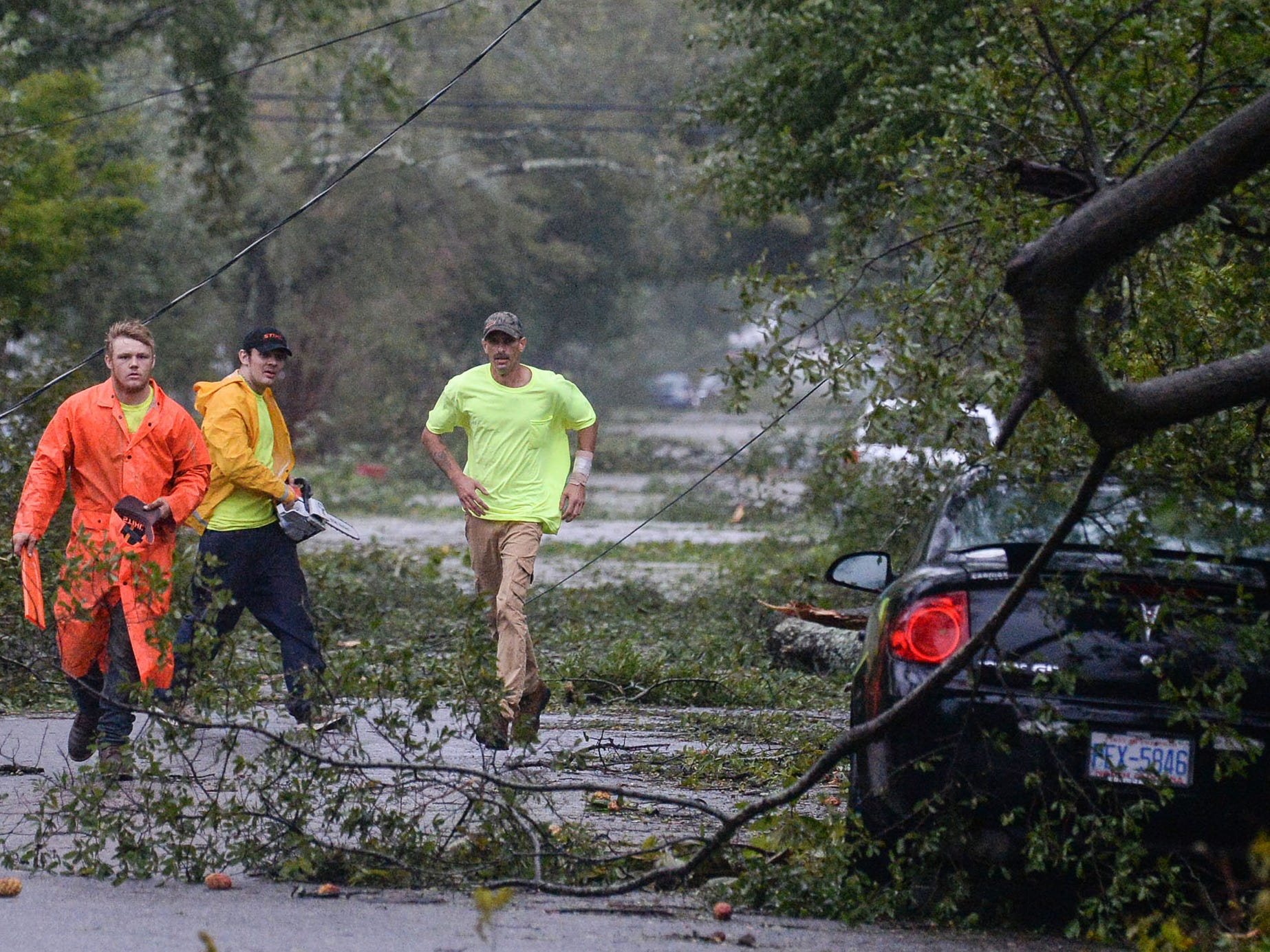 Men from a tree cutting service help clear a blocked road near downtown Wilmington, North Carolina, on Friday, September 14, 2018. (Ken Ruinard / Greenville News / Gannett USA Today Network / 2018 )