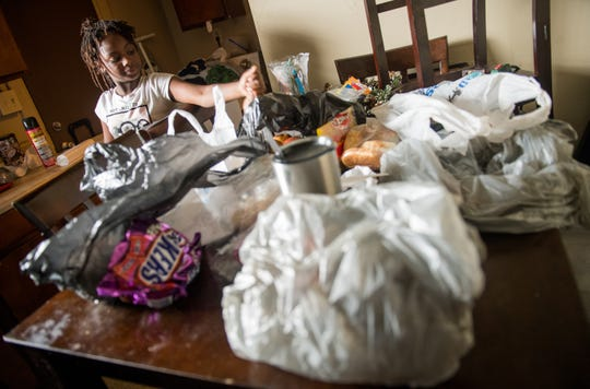 9/13/18 2:20:06 PM -- Charleston, SC, U.S.A  -- Taliyah Wright-Crosby, 11, organizes Hurricane Florence supplies while watching her mother Arlean Wright-Crosby prepare dinner for her family in their home as they settle in to ride out Hurricane Florence along with other neighbors on Romney Street in Charleston before Hurricane Florence makes landfall along the East Coast.  --    Photo by Jack Gruber, USA TODAY staff
