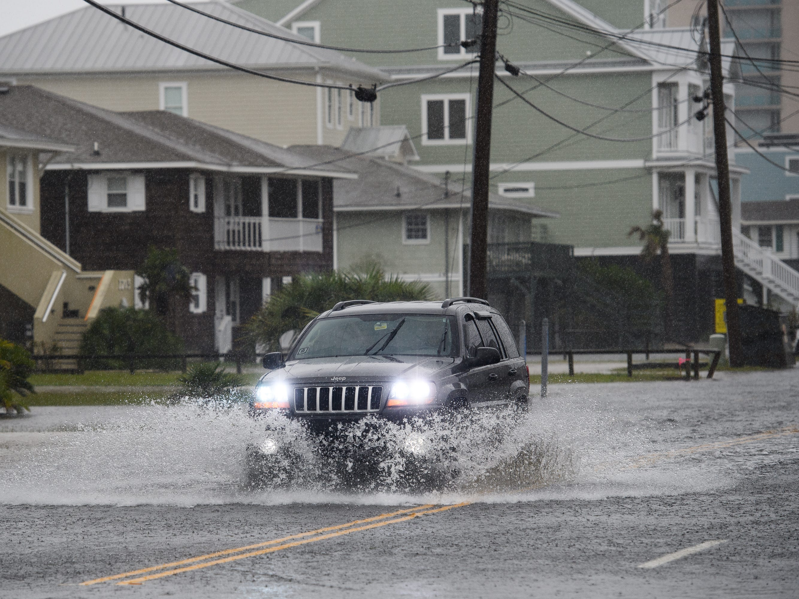 A motorist drives down North Ocean Boulevard in North Myrtle Beach as it begins to flood on Friday, Sept. 14, 2018.