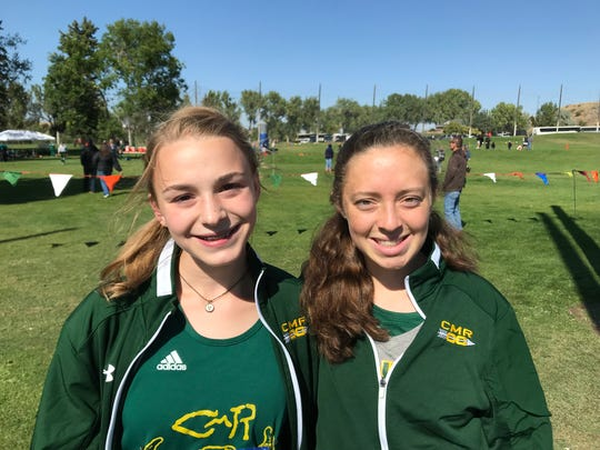 CMR's Emma Bergman, left, and Alyssa Tomlinson smile in the sunshine during Friday's Great Falls Invitational cross country meet at Anaconda Hills Golf Course.