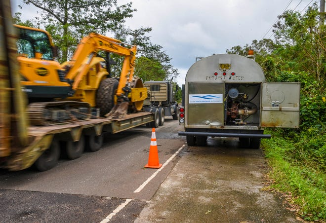 A tractor hauling heavy machinery passes a Guam Waterworks Authority water tanker positioned along Route 2, near the Adventist World Radio site, in upper Santa Ana, Agat on Friday, Sept. 14, 2018. The tanker, and another in Malesso, were made available to provide potable water to area residents experiencing water outages because the reservoir tanks were reported to have been lacking power or back-up generators to energize booster pumps that distributes water to people living at the higher elevations.