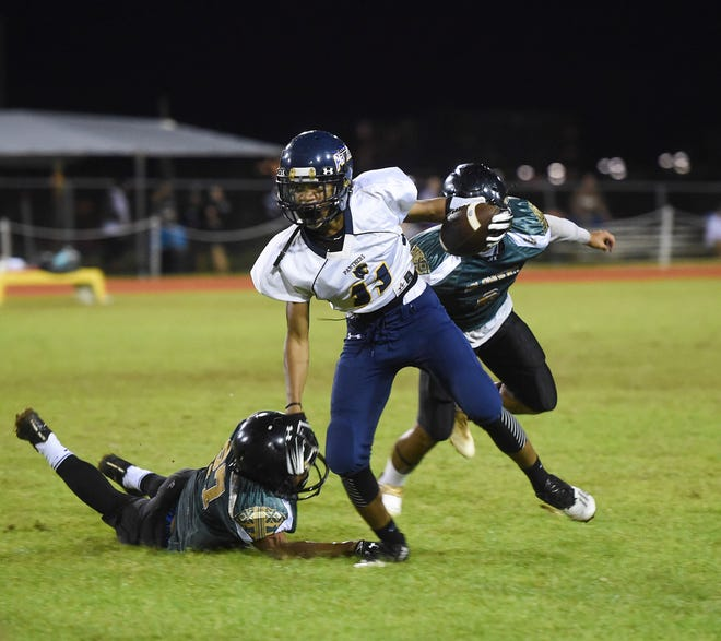 Guam High player Elijah Ferrell-Ayers breaks a tackle in an IIAAG High School Football game against the John F. Kennedy Islanders at Ramsey Field on Sept. 14, 2018. The Panthers won the contest 13-6 in overtime.