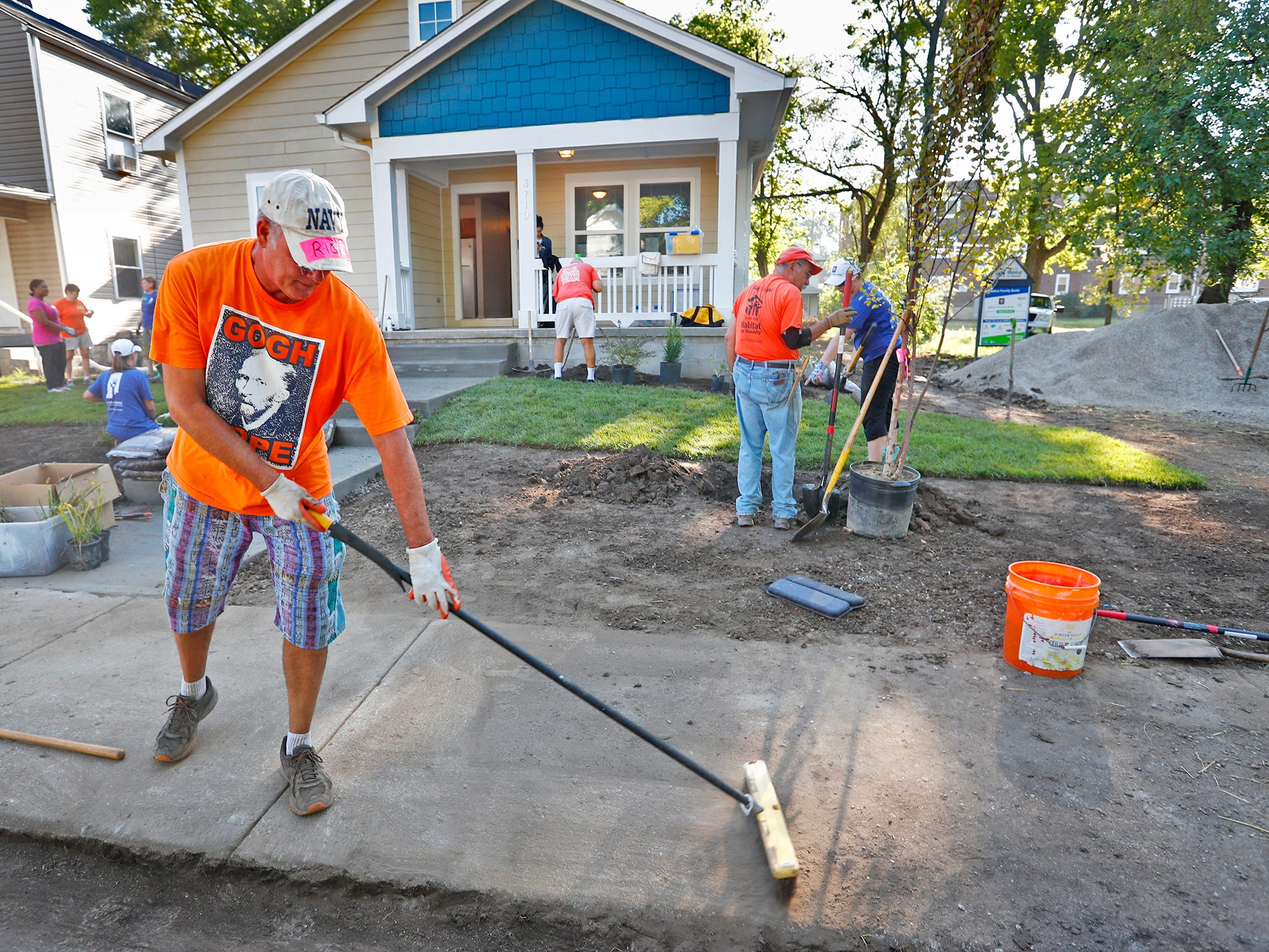 Rick Wurster sweeps the front sidewalk of a Habitat for Humanity home, during the 10th Annual IU Health Day of Service, Friday, Sept. 13, 2018.  IU Health team members donated time and effort building and finishing a Habitat for Humanity home in the 3700 block of Kenwood Ave. For 22 days, with partner volunteers, over 250 members of the IU Health team have donated more than 1680 hours at the house that will become the new home for the Ndatira family.