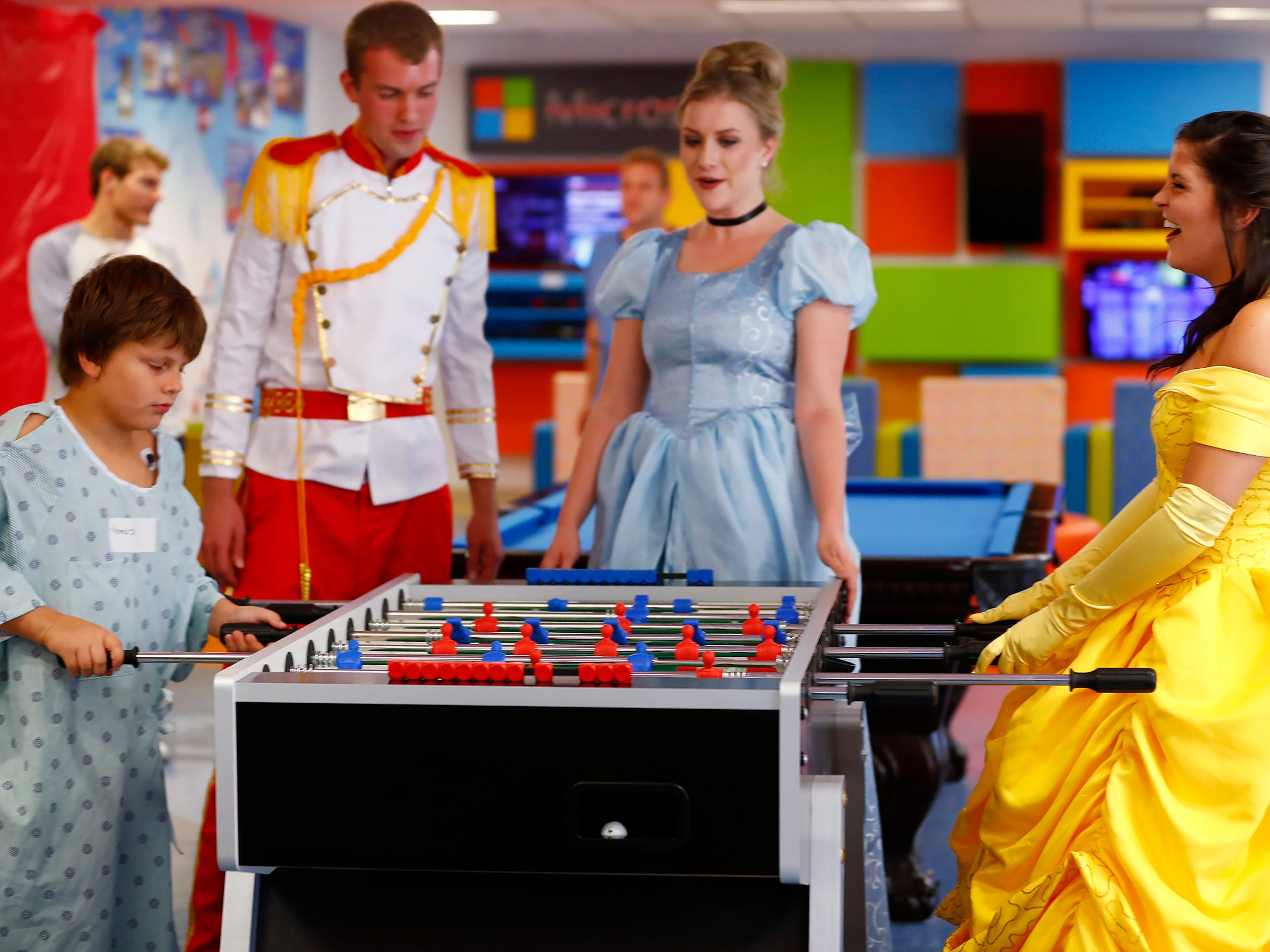"Thomas Gibbons, left, plays table hockey with ""Belle,"" Brooke Barnes, right, as ""Prince Charming,"" Grayson Faircloth and ""Cinderella,"" Haley Sample, look on, at Riley Children's Health, Friday, Sept. 13, 2018. IU students with ""Royal Encounters"" entertained patients and their families at Riley.  Princesses and a Prince, with the volunteer group, brought smiles to the kids with their visit."