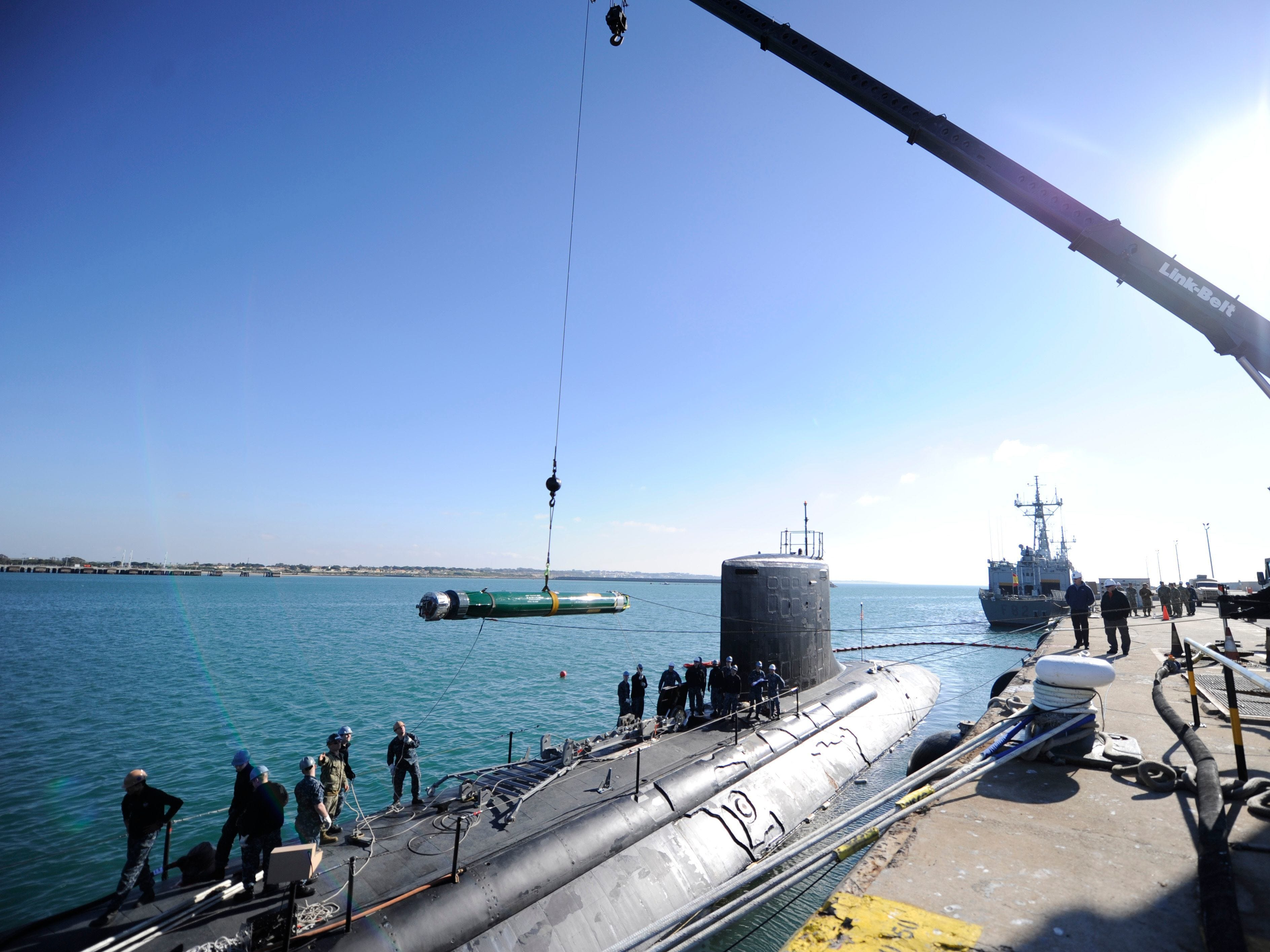 Sailors load a training torpedo into the USS California during an exercise in Spain in January. The Navy will christen this sub's sister-ship, the USS Indiana, on Saturday.