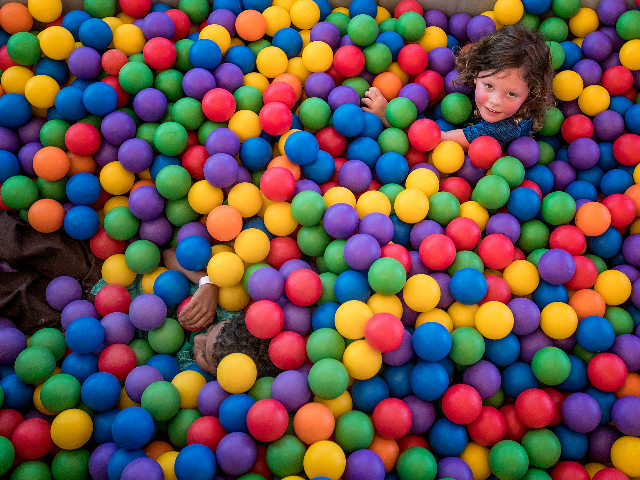 Children swim around in a ball pit, part of the Big Bounce America inflatable attraction at Waterman's Family Farm in Indianapolis, Friday, Sept. 14, 2018. The world's largest bounce house covers 10,000 square feet and will be in Indy though September 16.