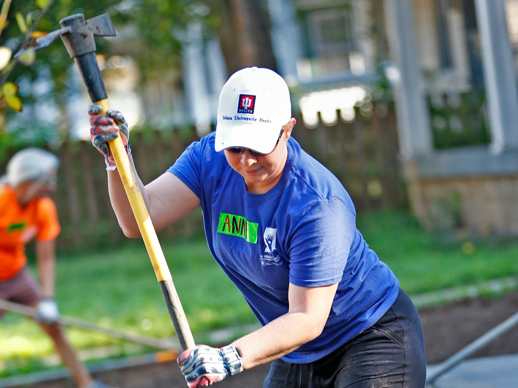 Annie Montz swings a pickaxe while working on landscaping, during the 10th Annual IU Health Day of Service, Friday, Sept. 13, 2018.  IU Health team members donated time and effort building and finishing a Habitat for Humanity home in the 3700 block of Kenwood Ave. For 22 days, with partner volunteers, over 250 members of the IU Health team have donated more than 1680 hours at the house that will become the new home for the Ndatira family.