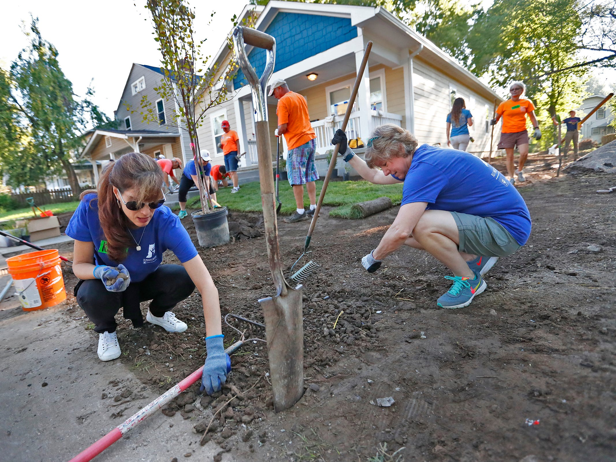 Katie Du Fresne, left, Sharon Whitaker, right, and other volunteers work on front lawn landscaping during the 10th Annual IU Health Day of Service, Friday, Sept. 13, 2018.  IU Health team members donated time and effort building and finishing a Habitat for Humanity home in the 3700 block of Kenwood Ave. For 22 days, with partner volunteers, over 250 members of the IU Health team have donated more than 1680 hours at the house that will become the new home for the Ndatira family.