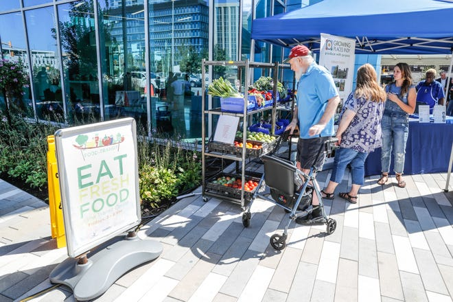 Customer and IndyGo Transit Ambassador, Bob Skinner, left, and Hope Moran, center, look over fresh produce during the launch of the ÒFood in TransitÓ program at the Julia M. Carson Transit Center on Friday, Sept. 14, 2018. Visitors to the Transit Center can purchase produce every Friday from 3 p.m. to 6 p.m. through October 26.