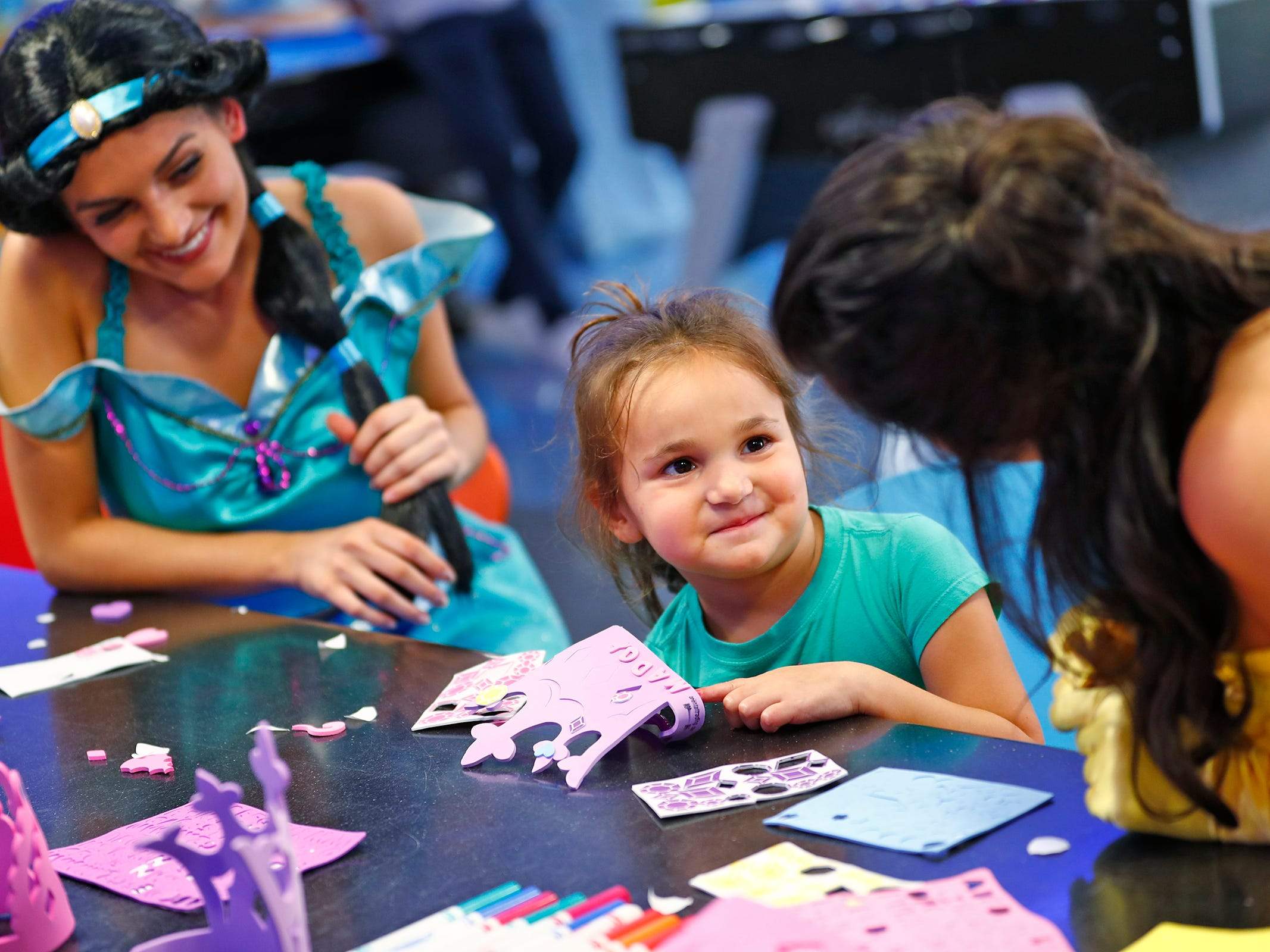 "Maddy McCombs, center, makes crowns with princesses ""Jasmine,"" Hannah Cotter, and ""Belle,"" Brooke Barnes, at Riley Children's Health, Friday, Sept. 13, 2018.  IU students with ""Royal Encounters"" entertained patients and their families at Riley.  Princesses and a Prince, with the volunteer group, brought smiles to the kids with their visit."