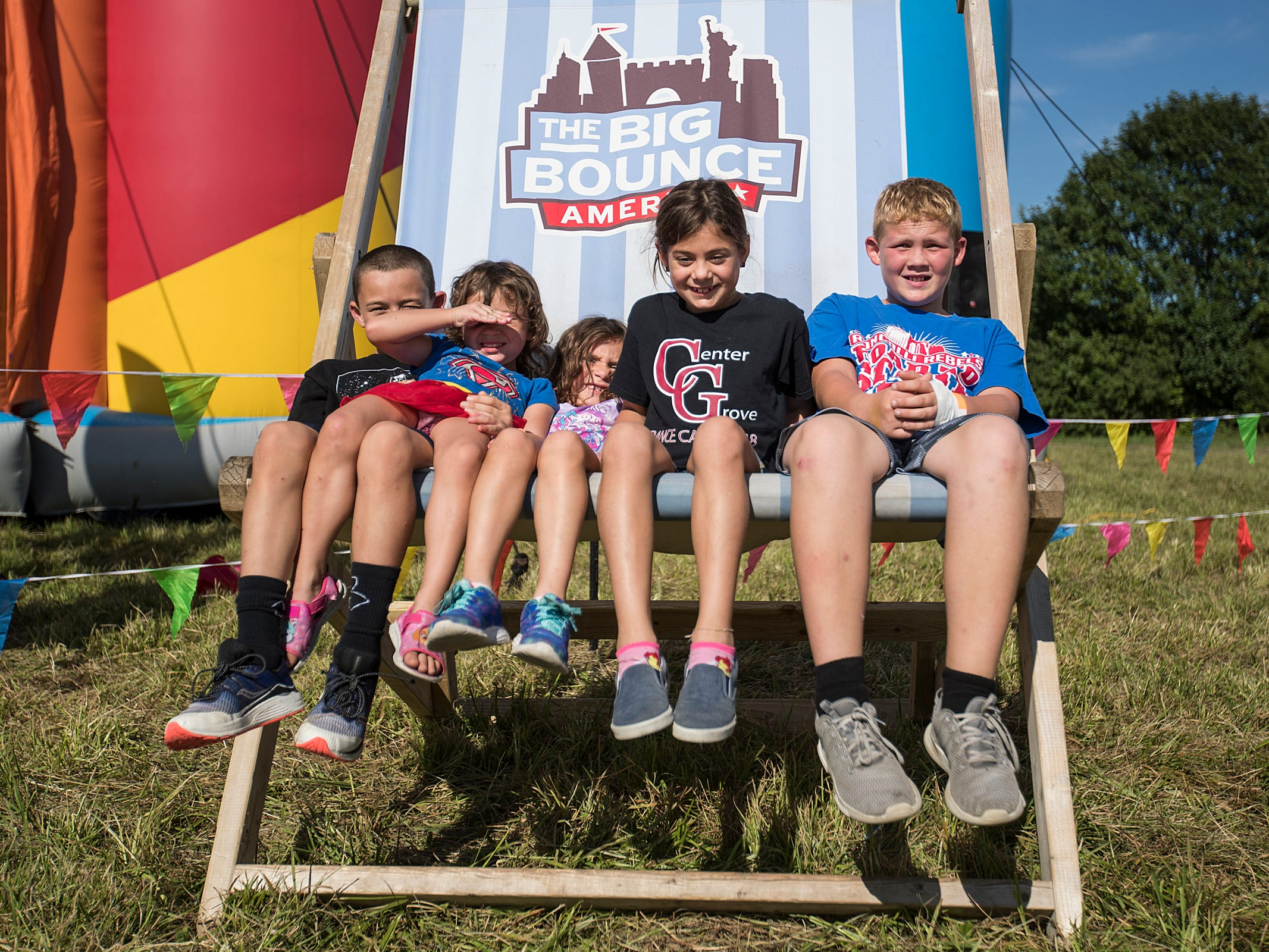 Kids sit for a picture on a giant lawn chair in front of the Big Bounce America inflatable attraction at Waterman's Family Farm in Indianapolis, Friday, Sept. 14, 2018. The world's largest bounce house covers 10,000 square feet and will be in Indy though September 16.