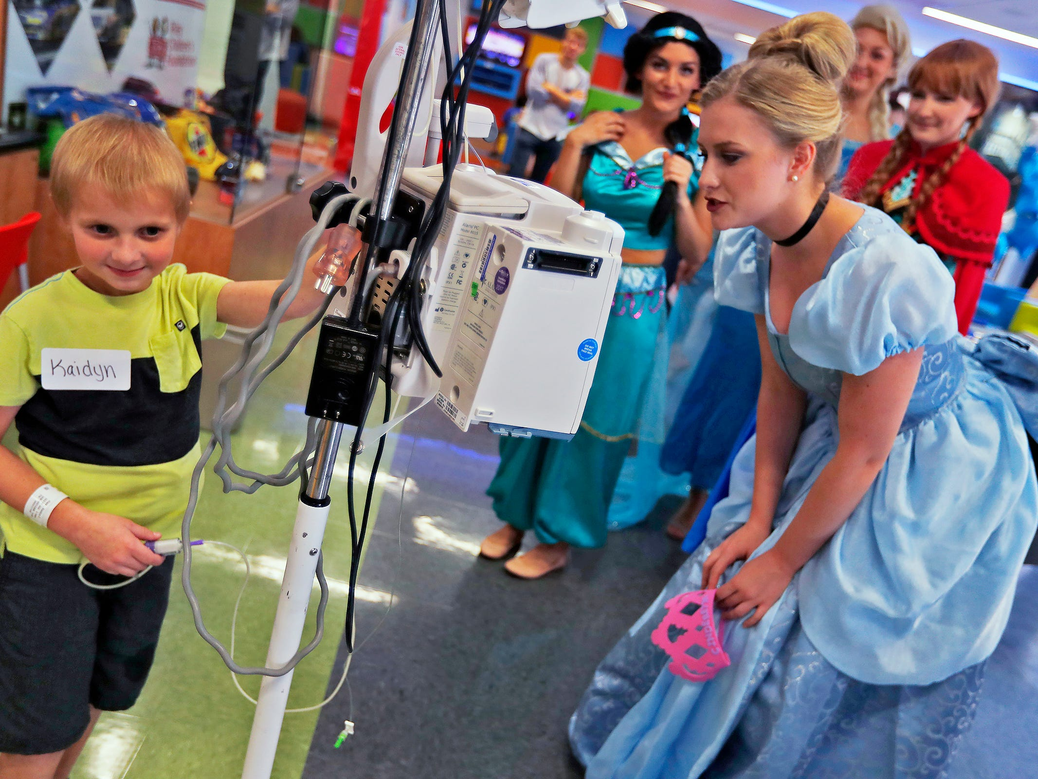 "Kaidyn Hazel, left, visits with ""Cinderella,"" Haley Sample, and other princesses at Riley Children's Health, Friday, Sept. 13, 2018. IU students with ""Royal Encounters"" entertained patients and their families at Riley.  Princesses and a Prince, with the volunteer group, brought smiles to the kids with their visit."
