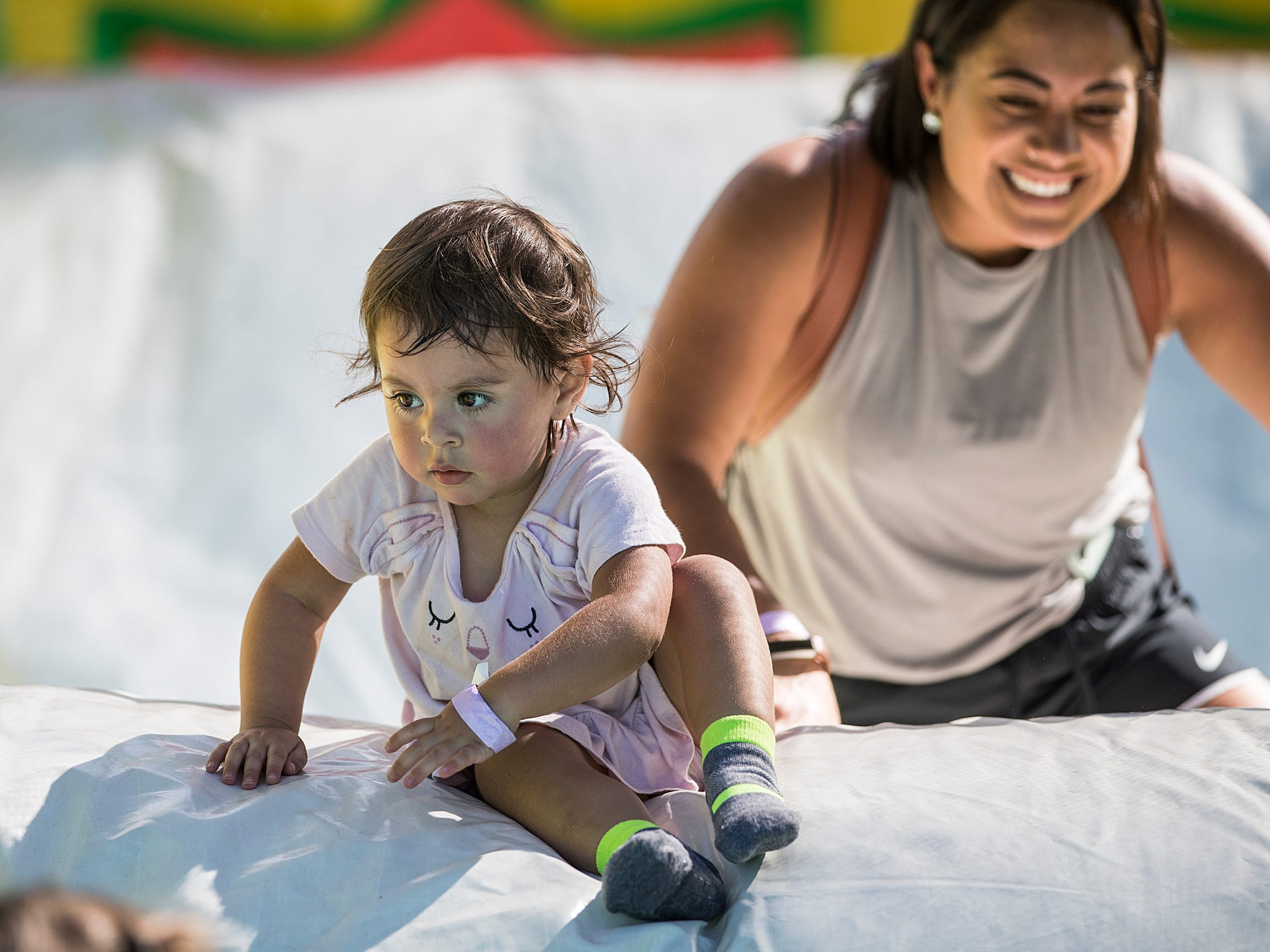Emma Mercer, 2, climbs over an inflated slide followed by her mother Cynthia Zimla, on the Big Bounce America attraction at Waterman's Family Farm in Indianapolis, Friday, Sept. 14, 2018. The world's largest bounce house covers 10,000 square feet and will be in Indy though September 16.