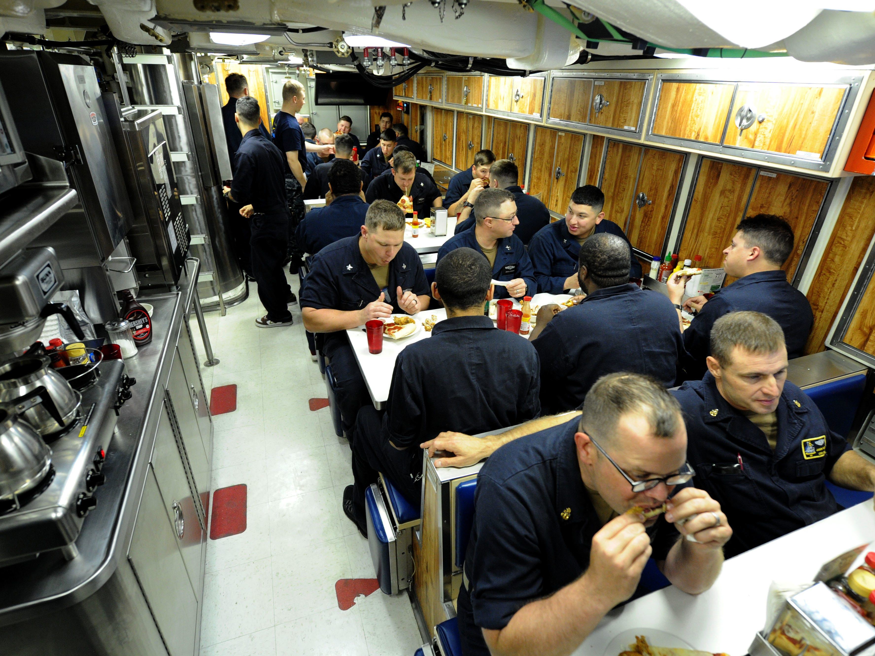 Sailors assigned to Pre-Commissioning Unit Indiana (SSN 789) eat dinner in the crew's mess while underway, June 23, 2018. Indiana is the 16th Virginia-class fast attack submarine and is scheduled to be commissioned Sept. 29, 2018.  (U.S. Navy photo by Chief Mass Communication Specialist Darryl Wood/Released)