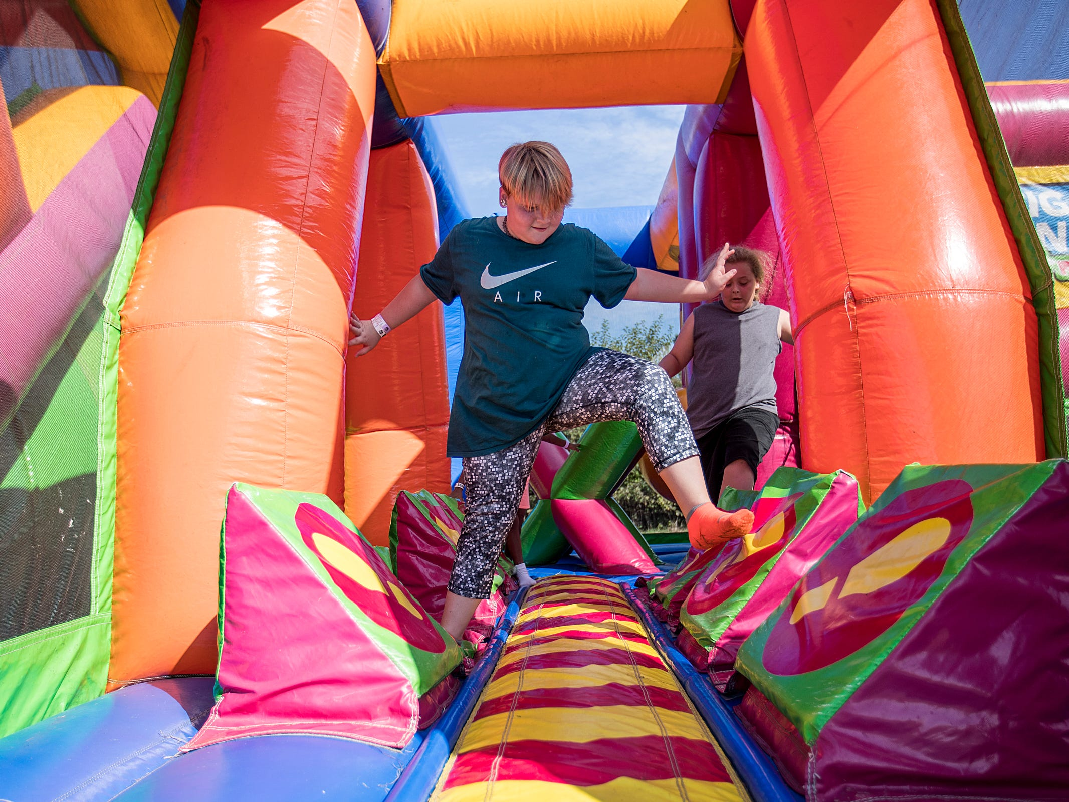 Lily Ent, 11, makes her way through an inflated obstacle course, part of the Big Bounce America attraction at Waterman's Family Farm in Indianapolis, Friday, Sept. 14, 2018. The world's largest bounce house covers 10,000 square feet and will be in Indy though September 16.