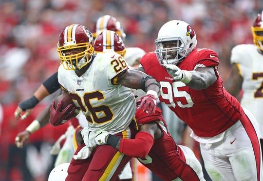 Sep 9, 2018;  Washington Redskins running back Adrian Peterson (26) is pursued by Arizona Cardinals defensive tackle Rodney Gunter (95) at State Farm Stadium.