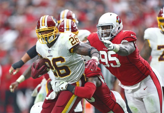 Sep 9, 2018;  Washington Redskins running back Adrian Peterson (26) is pursued by Arizona Cardinals defensive tackle Rodney Gunter (95) at State Farm Stadium.