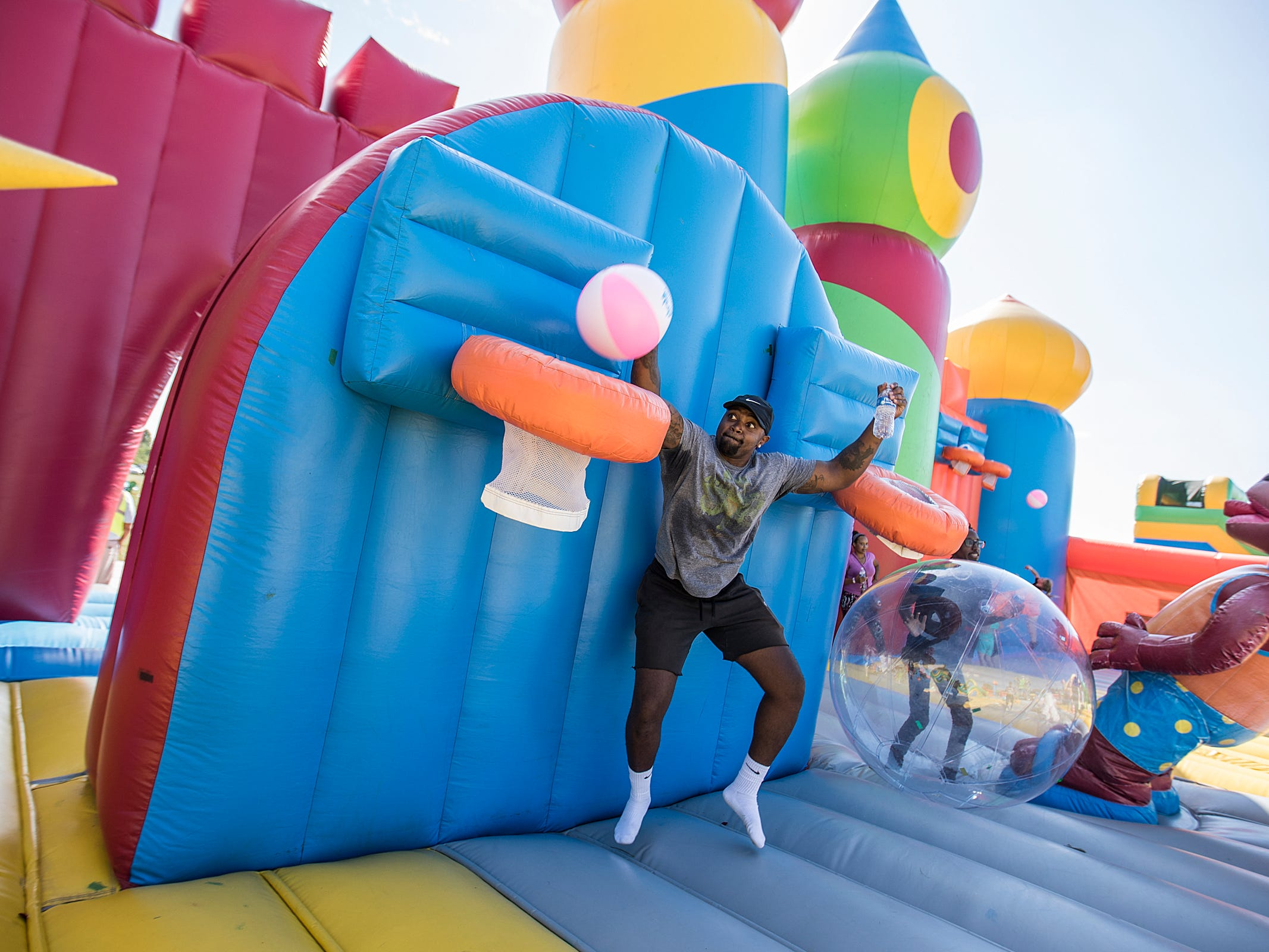 Johnnie Long slams a dunk inside the Big Bounce America inflatable attraction at Waterman's Family Farm in Indianapolis, Friday, Sept. 14, 2018. The world's largest bounce house covers 10,000 square feet and will be in Indy though September 16.