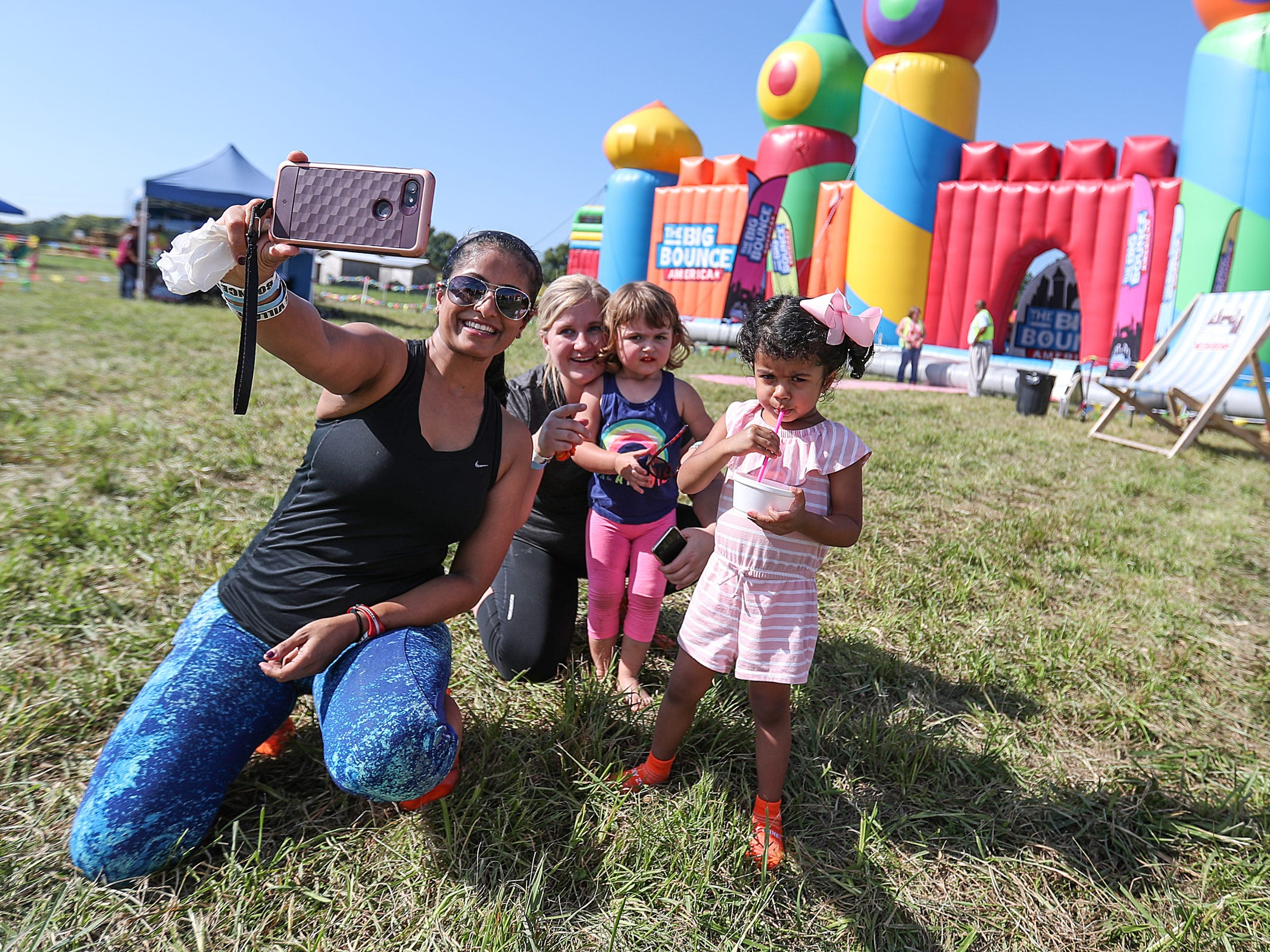 A group takes a selfie in front of the Big Bounce America inflatable attraction at Waterman's Family Farm in Indianapolis, Friday, Sept. 14, 2018. The world's largest bounce house covers 10,000 square feet and will be in Indy though September 16.