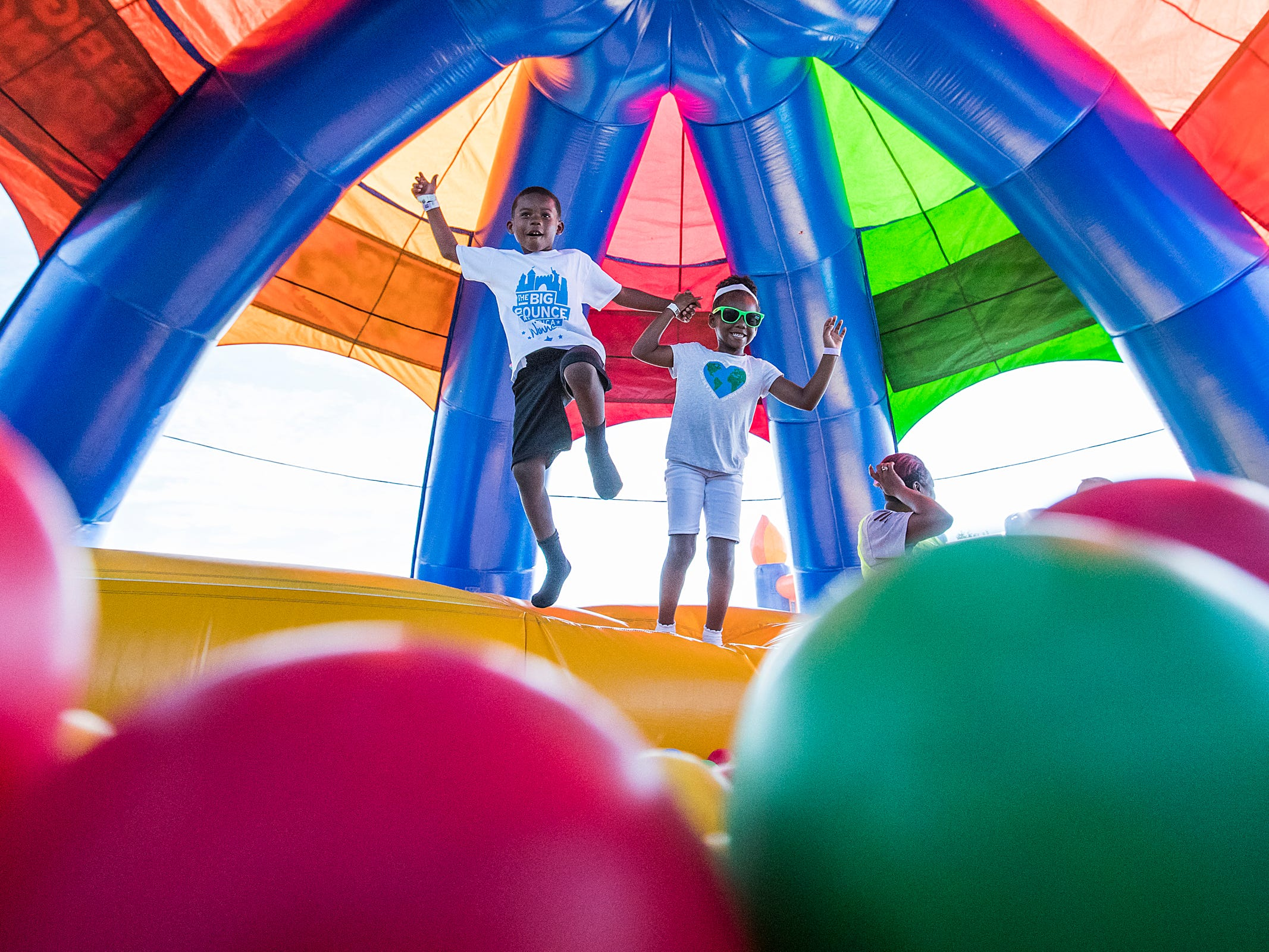 Carter Lewis, 7, and Kennedy Lewis, 5, hold hands as they jump into a ball pit together inside the Big Bounce America inflatable attraction at Waterman's Family Farm in Indianapolis, Friday, Sept. 14, 2018. The world's largest bounce house covers 10,000 square feet and will be in Indy though September 16.