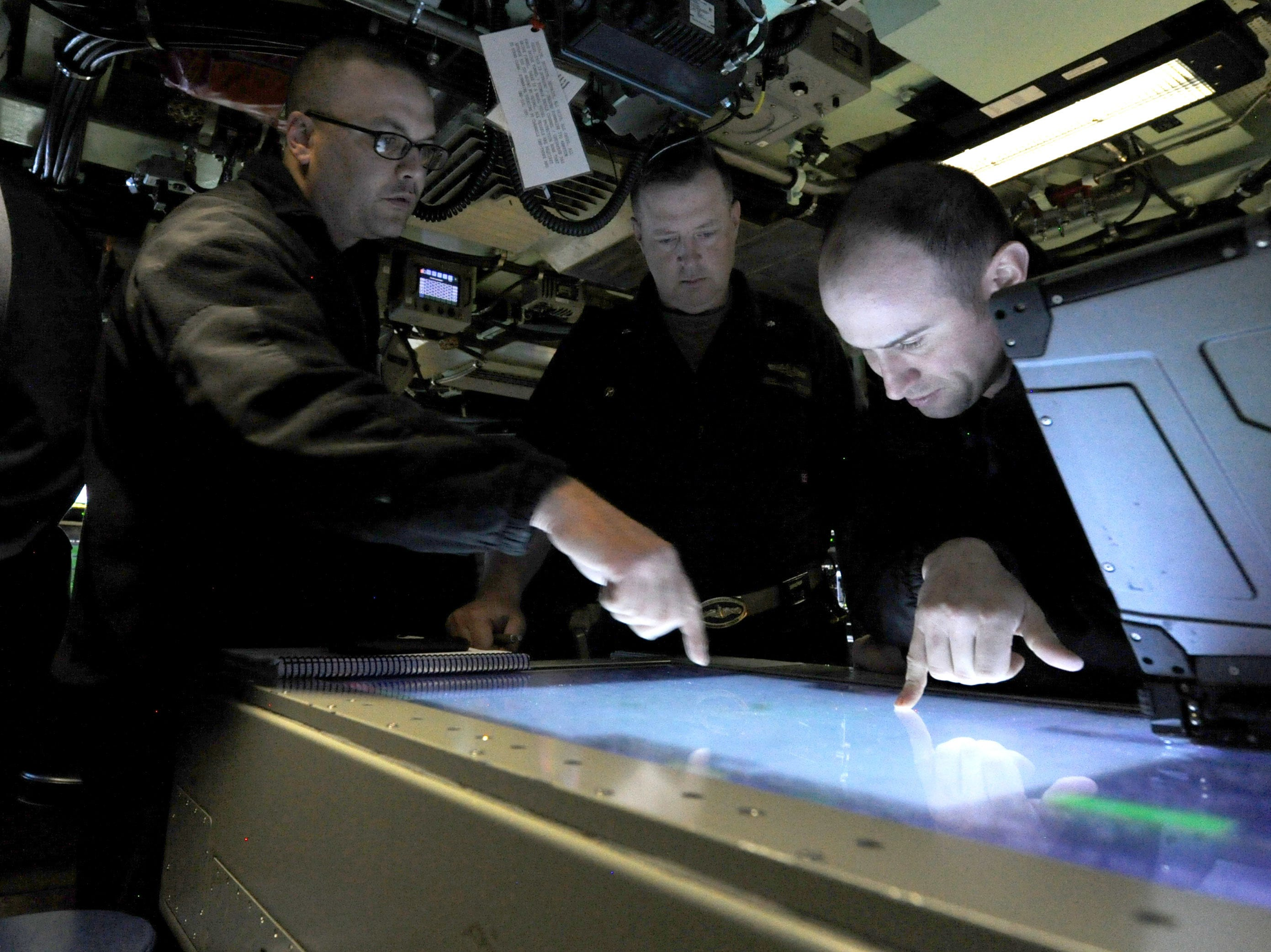Cmdr. Jesse Zimbauer, center, commanding officer of Pre-Commissioning Unit Indiana (SSN 789) observes the review of navigational charts while underway, June 24, 2018. Indiana is the 16th Virginia-class fast attack submarine and is scheduled to be commissioned Sept. 29, 2018. (U.S. Navy photo by Chief Mass Communication Specialist Darryl Wood/Released
