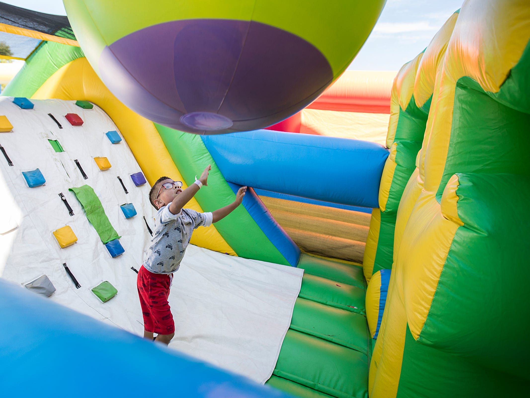 Kids and parents play in the Big Bounce America inflatable attraction at Waterman's Family Farm in Indianapolis, Friday, Sept. 14, 2018. The world's largest bounce house covers 10,000 square feet and will be in Indy though September 16.