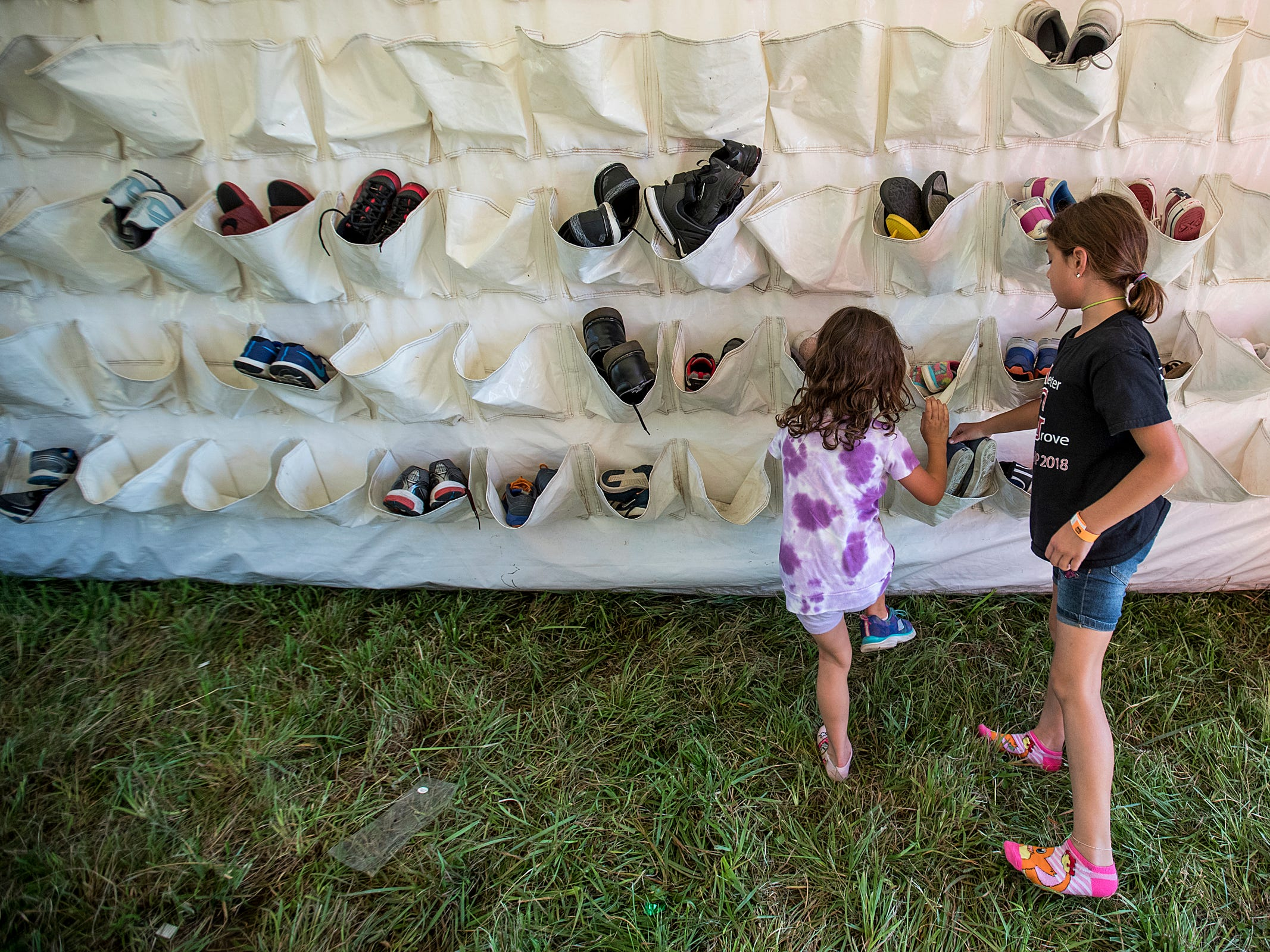 Children leave their shoes as they head for the Big Bounce America inflatable attraction at Waterman's Family Farm in Indianapolis, Friday, Sept. 14, 2018. The world's largest bounce house covers 10,000 square feet and will be in Indy though September 16.