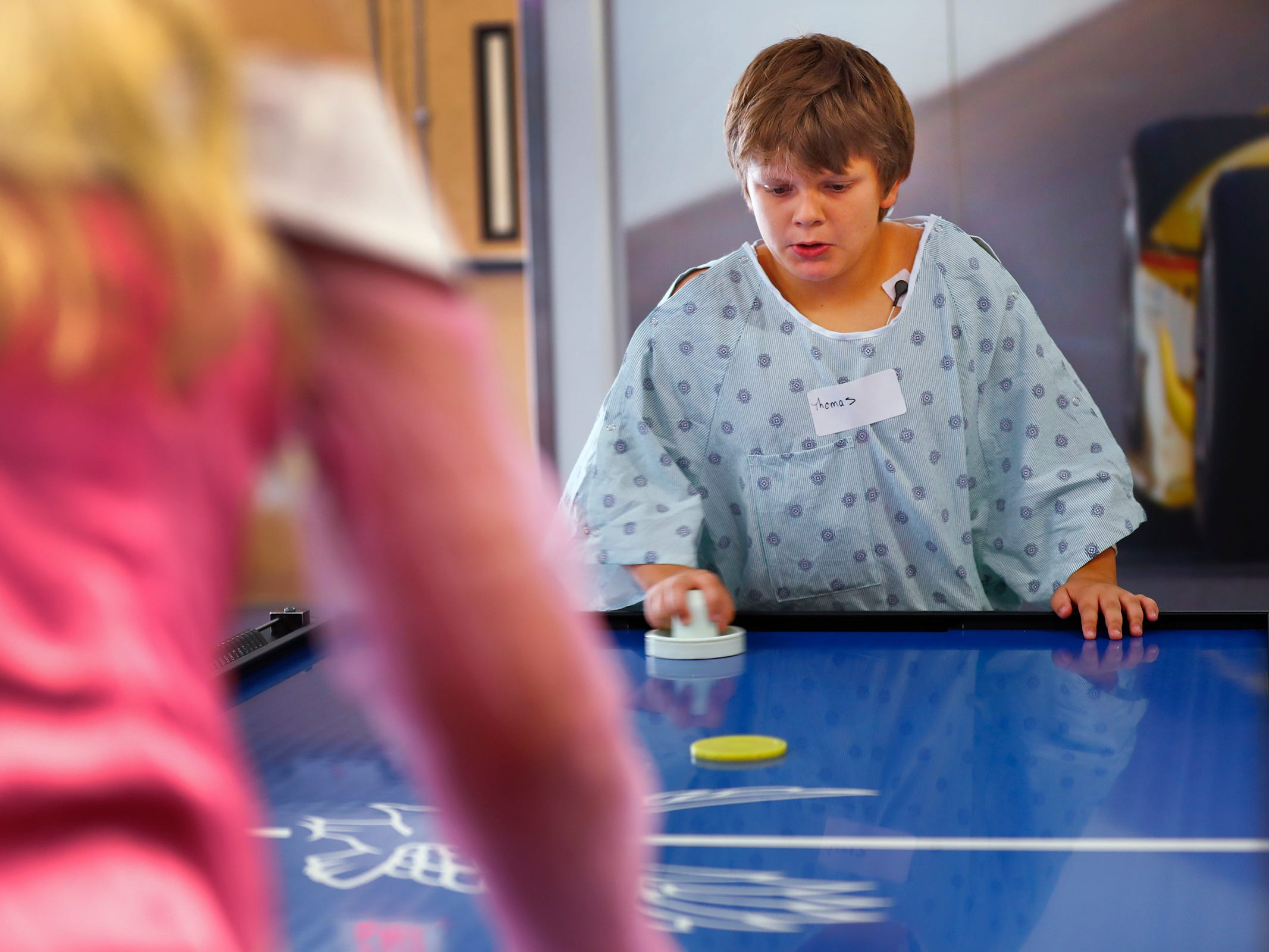 "Thomas Gibbons, right, plays air hockey with ""Sleeping Beauty,"" Aaliyah Darling, at Riley Children's Health, Friday, Sept. 13, 2018.  IU students with ""Royal Encounters"" entertained patients and their families at Riley.  Princesses and a Prince, with the volunteer group, brought smiles to the kids with their visit."