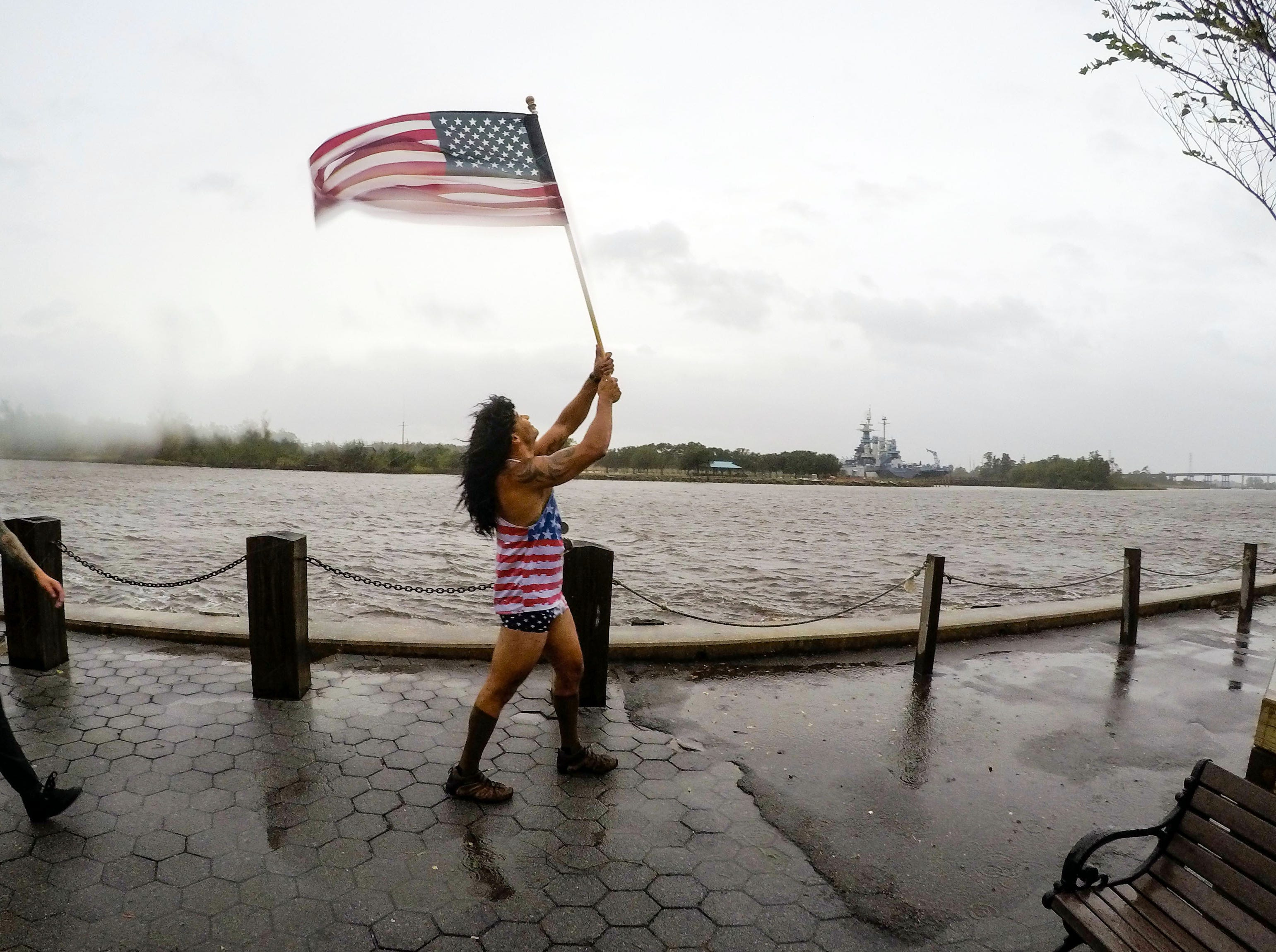 Sept 13, 2018; Wilmington, NC, USA; Jeff Egyp carries a United States flag in windy conditions along the Cape Fear River in downtown.