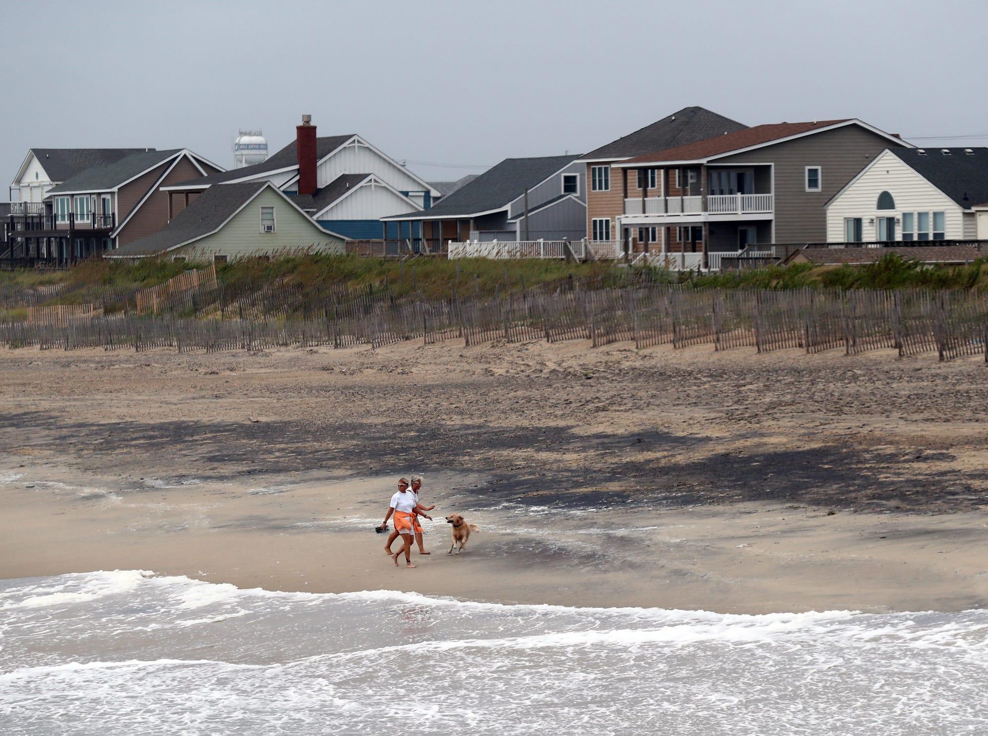 September 14, 2018; Kill Devil Hills, NC, USA; Local residents walk along the beach in Kill Devil Hills, North Carolina on Friday, September 14, 2018.