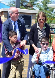 State Rep. Roger Kane and Knox Co. School Board Rep. Terry Hill help Anthony Sacco, 10, (front left) and Titus Satterfield, 12, cut the ribbon at the all-inclusive playground grand opening ceremony held at the facility on 6618 Beaver Ridge Rd. Sunday, May 7, 2017.