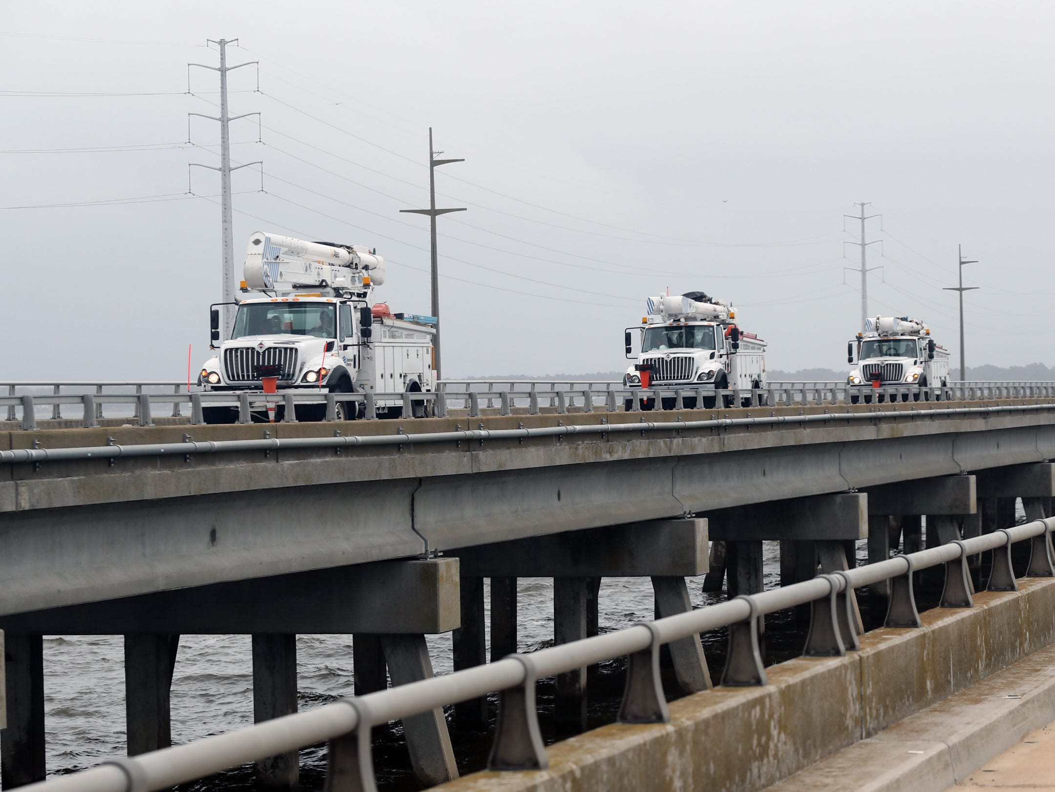 September 14, 2018; Kill Devil Hills, NC, USA; Utility trucks cross the causeway on the N. Croatan Highway from Kitty Hawk, North Carolina on Friday, September 14, 2018.