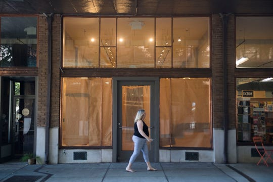 A pedestrian walks past the store front which Union Ave. Books is expanding into on Union Ave in downtown Knoxville, Friday, Sept. 14, 2018. The store is co-owned by Flossie McNabb and her daughter Bunnie Presswood.