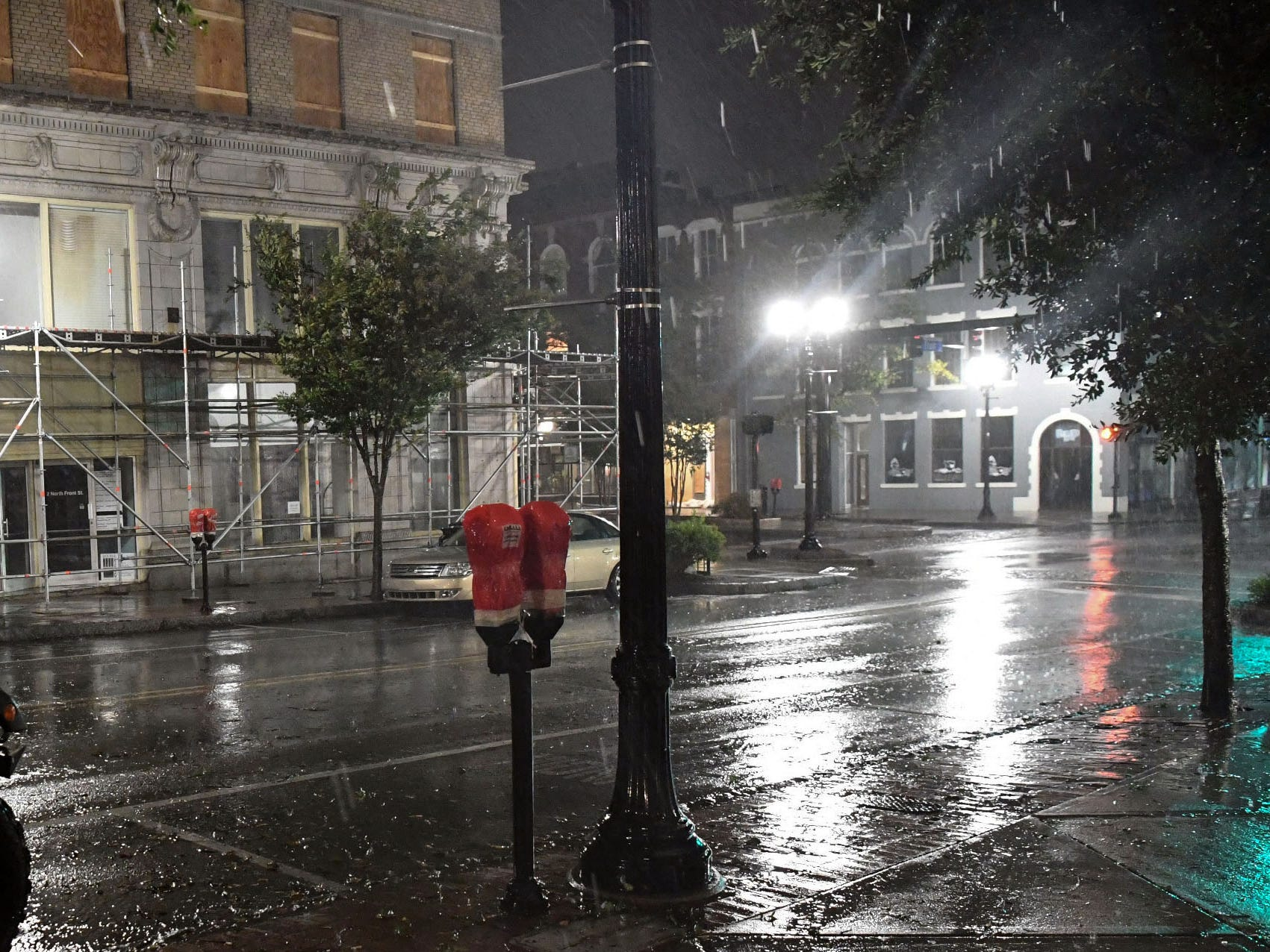 Sept 14, 2018; Wilmington, NC, USA; Windows and a parking meter is are covered while wind and rain gust early in the morning in downtown Wilmington, North Carolina. Mandatory credit: Ken Ruinard/Greenville News via USA Today Network