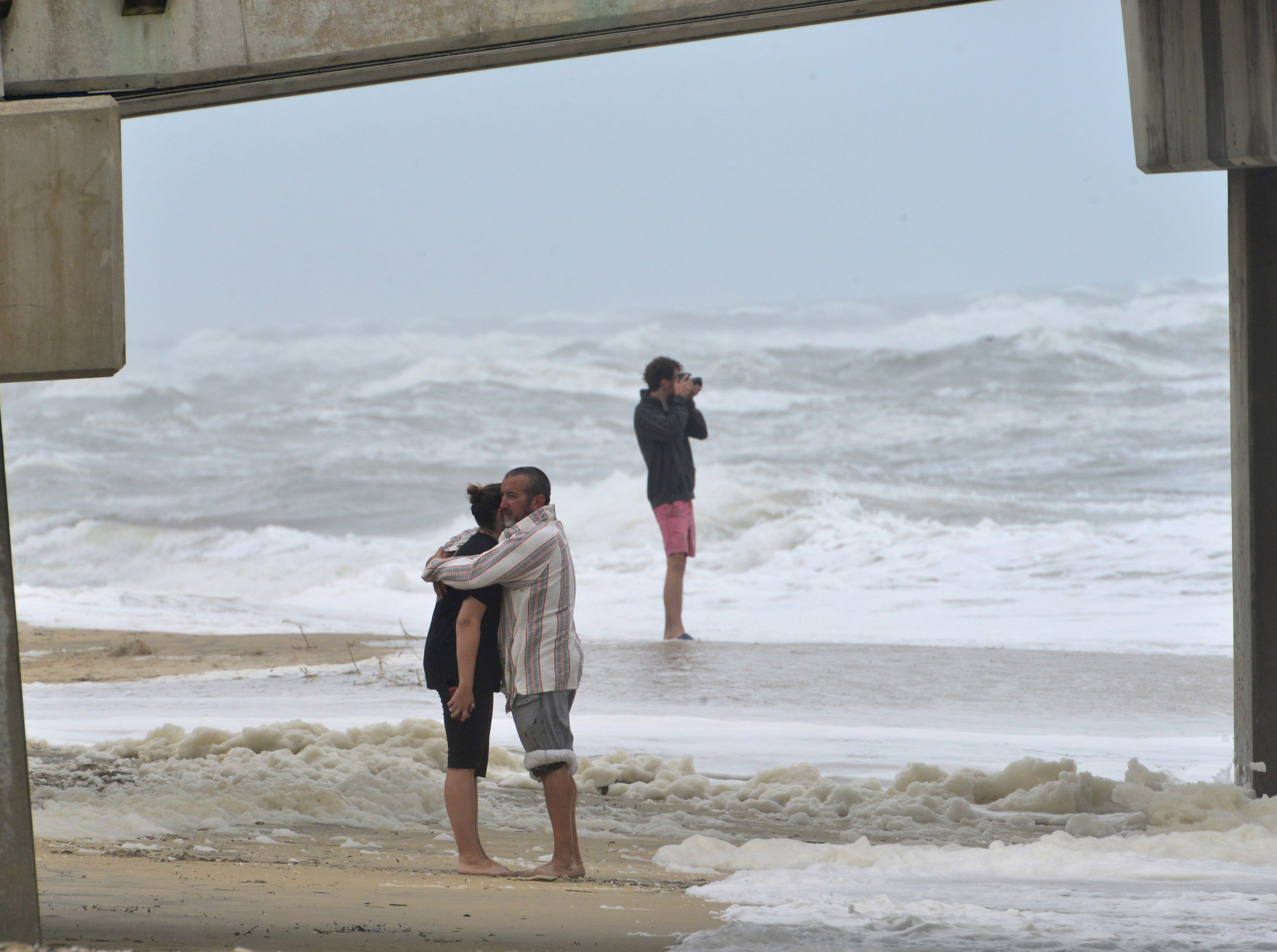 September 14, 2018; Nags Head, NC, USA; A couple hugs under Jennette's Pier in Nags Head, N.C. in the Outer Banks on Friday morning September 14, 2018.