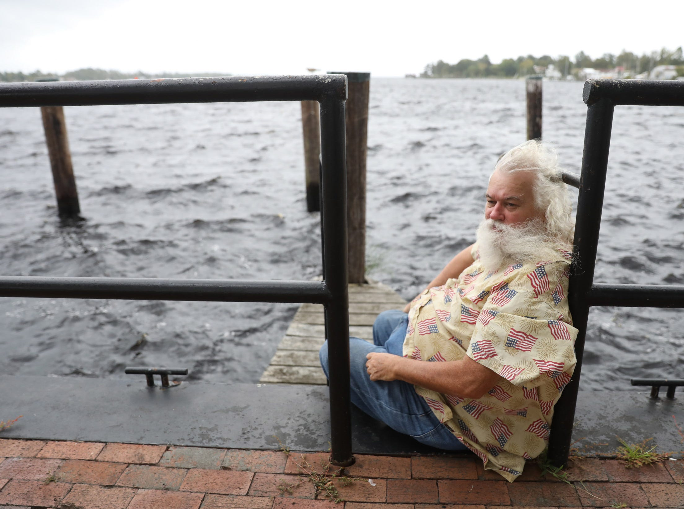Sep 13, 2018; Elizabeth City, NC, USA; Daniel Harris sits on the bulkheasd of  Mariners' wharf Park in downtown Elizabeth City, North Carolina on Thursday, September 13, 2018.  Harris plans to ride out the storm in his near by home.