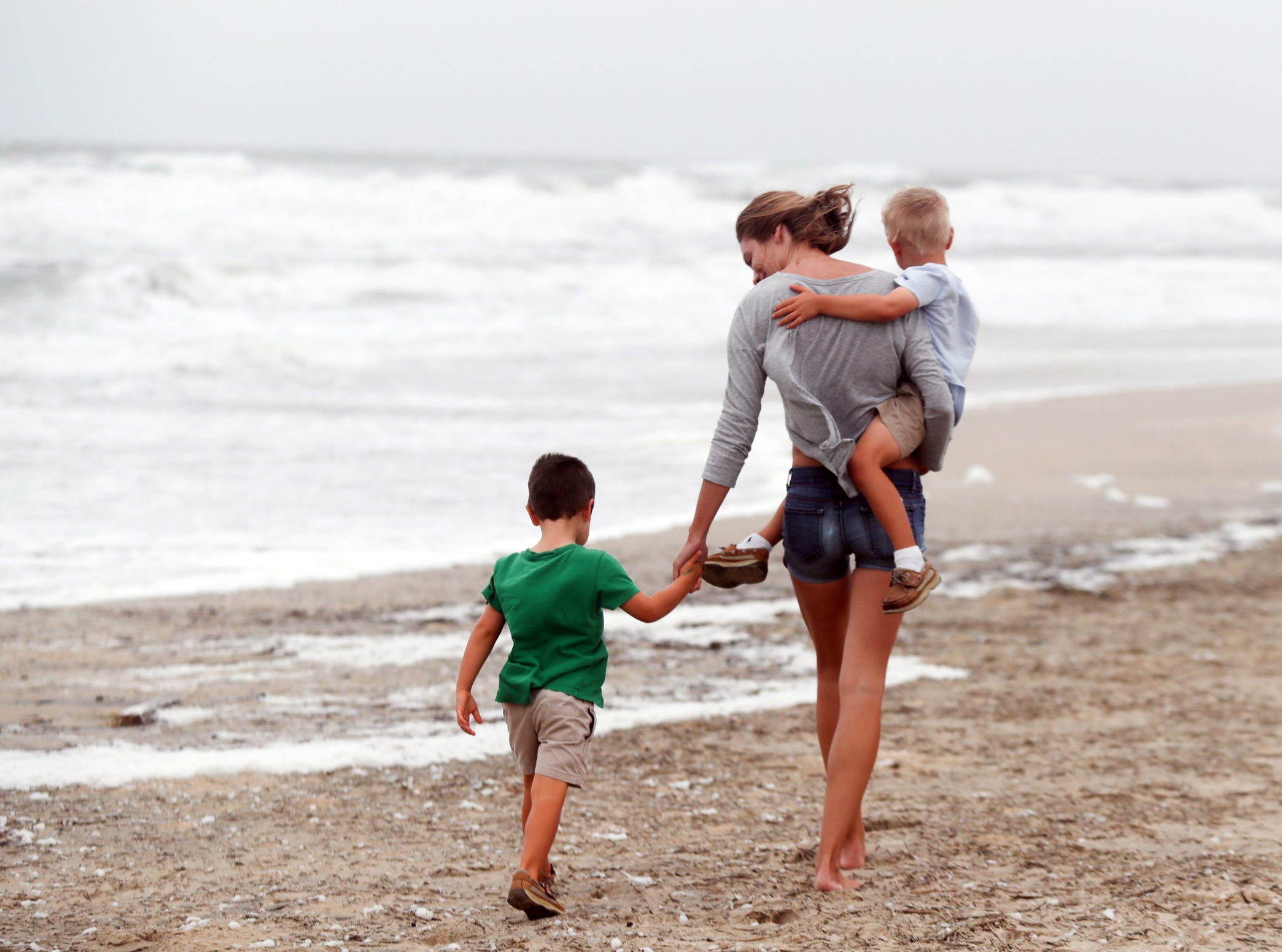 September 14, 2018; Nags Head, NC, USA; Creecy Richardson walks on the beach with her son's Winston and William in Nags Head, North Carolina on Friday, September 14, 2018.