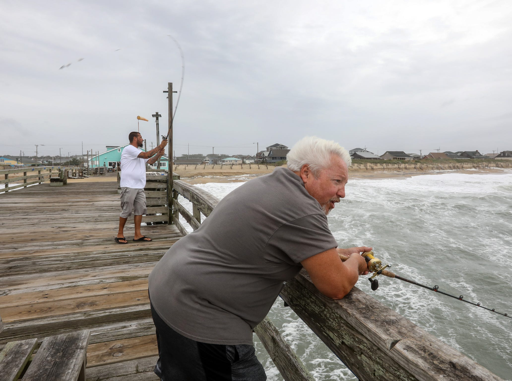 September 14, 2018; Kill Devil Hills, NC, USA; Troy Byrum, front, fishes off the Avalon Fishing Pier in Kill Devil Hills, North Carolina on Friday, September 14, 2018.