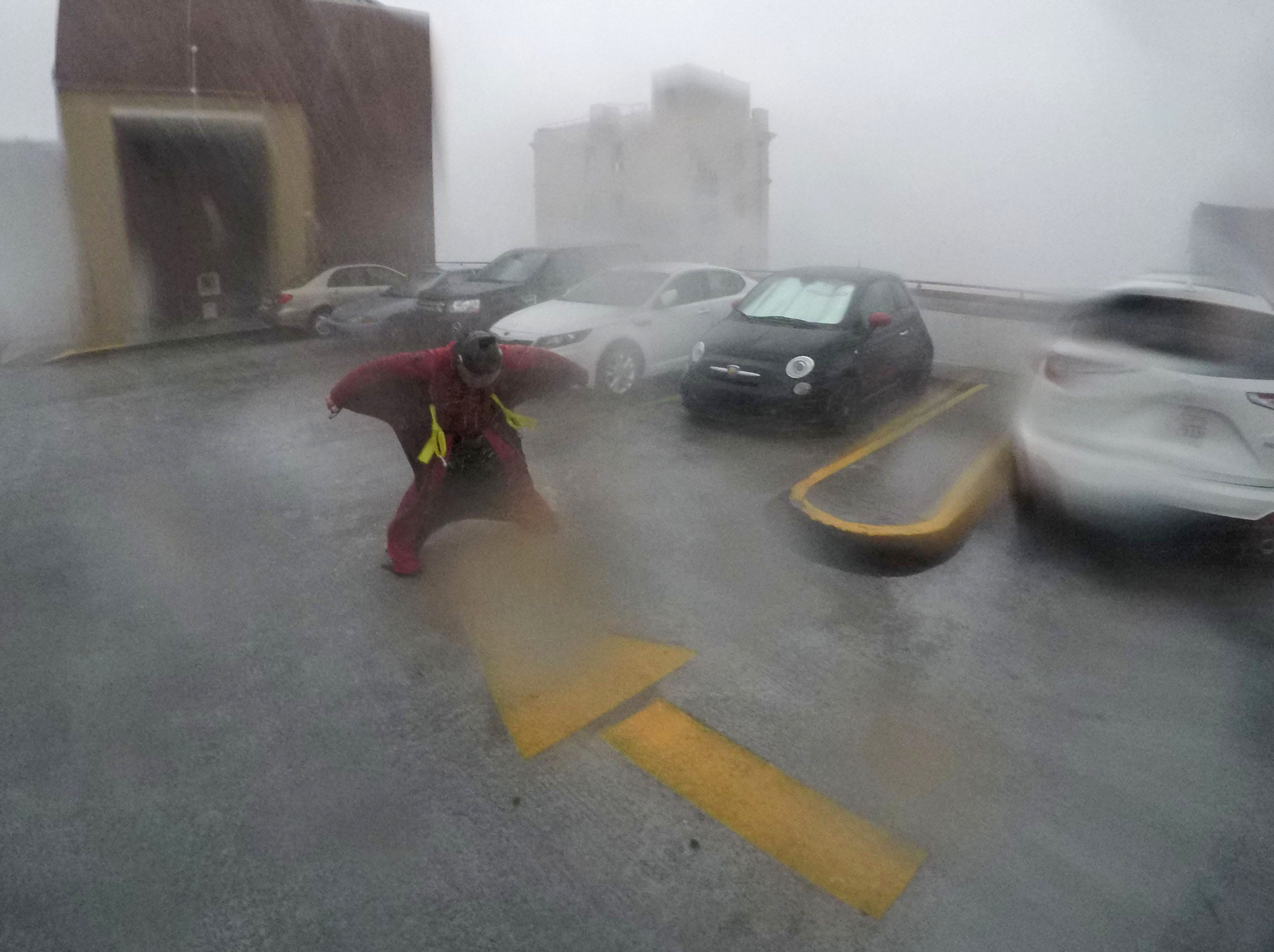 Sept 14, 2018; Wilmington, NC, USA; Michael Henderson of Tennessee, a professional skydiver, stands on the seventh floor of a parking garage in downtown Wilmington, North Carolina, as Hurricane Florence just hit land.
