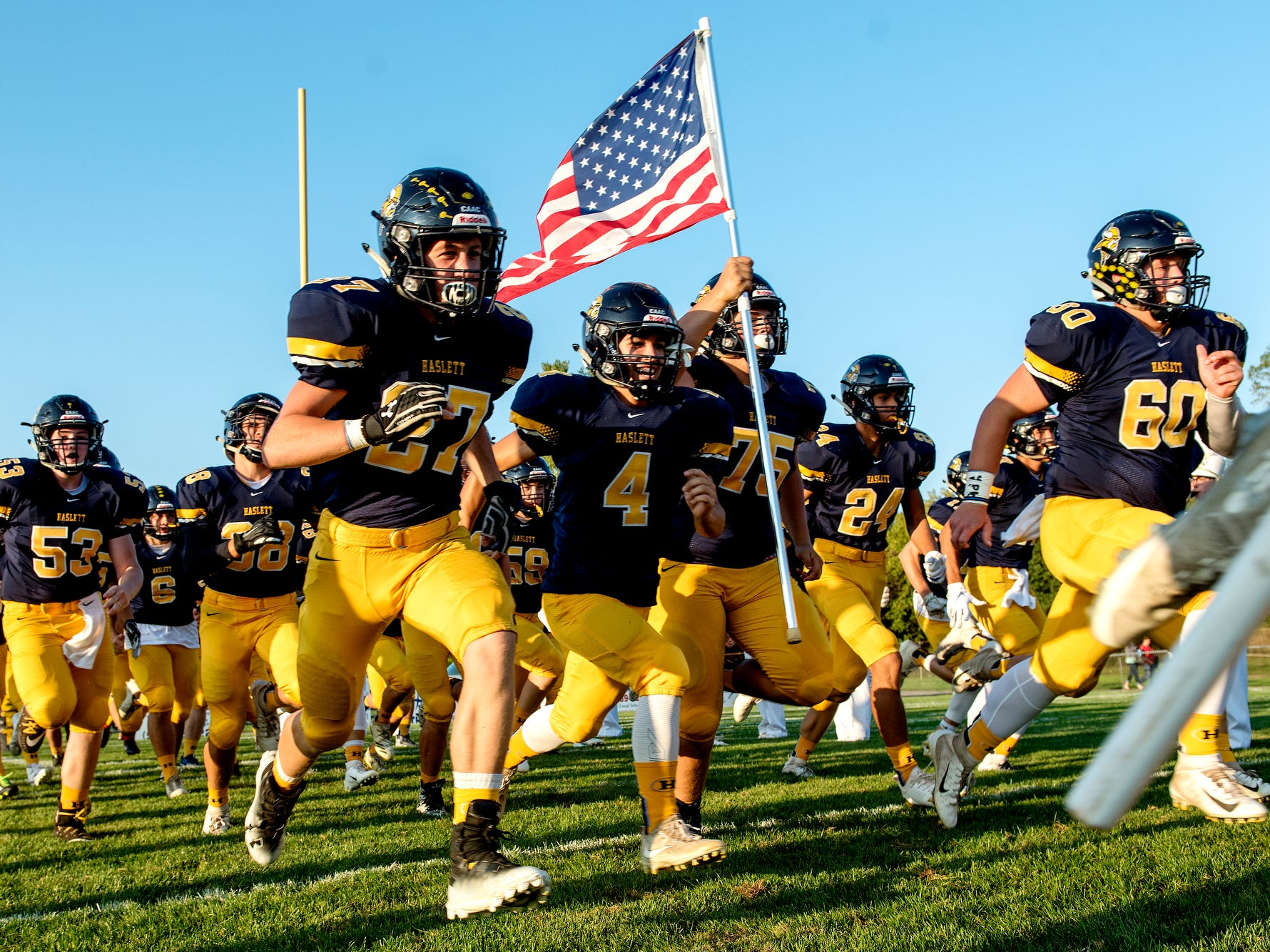 The Haslett football team takes the field before the Vikings' game against Fowlerville on Friday, Sept. 14, 2018, at Haslett High School.