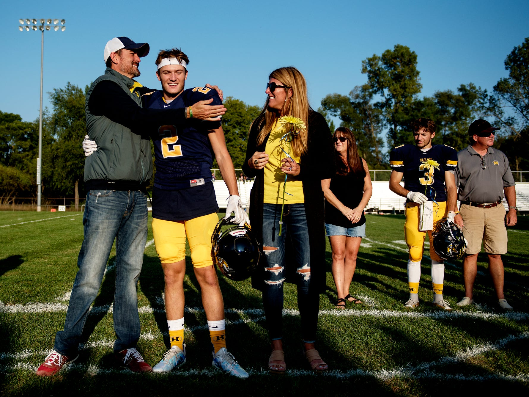 Haslett's Jaden Thelen, center, hugs his father Noel, left, as his mother Shannon looks on during a senior recognition ceremony before the Vikings' football game against Fowlerville on Friday, Sept. 14, 2018, at Haslett High School.