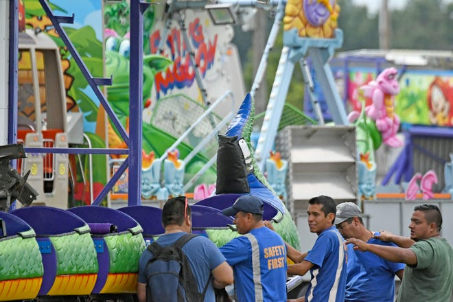 Workers from Bates Bros. Amusement Co. work on a ride Friday afternoon, preparing for the opening of the 2018 Ashland County Fair.