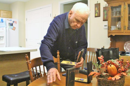 Charles Allen looks at some of his old medals on Tuesday. The 99-year-old will make the trip to Marion on Saturday, flying in an old Ford Tri-Motor.
