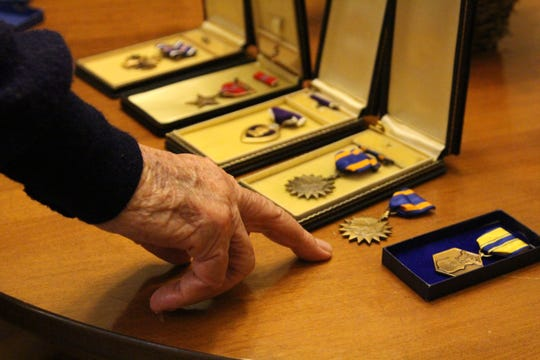 Charles Allen points to one of the medals that he earned during his 28 years as a military pilot.